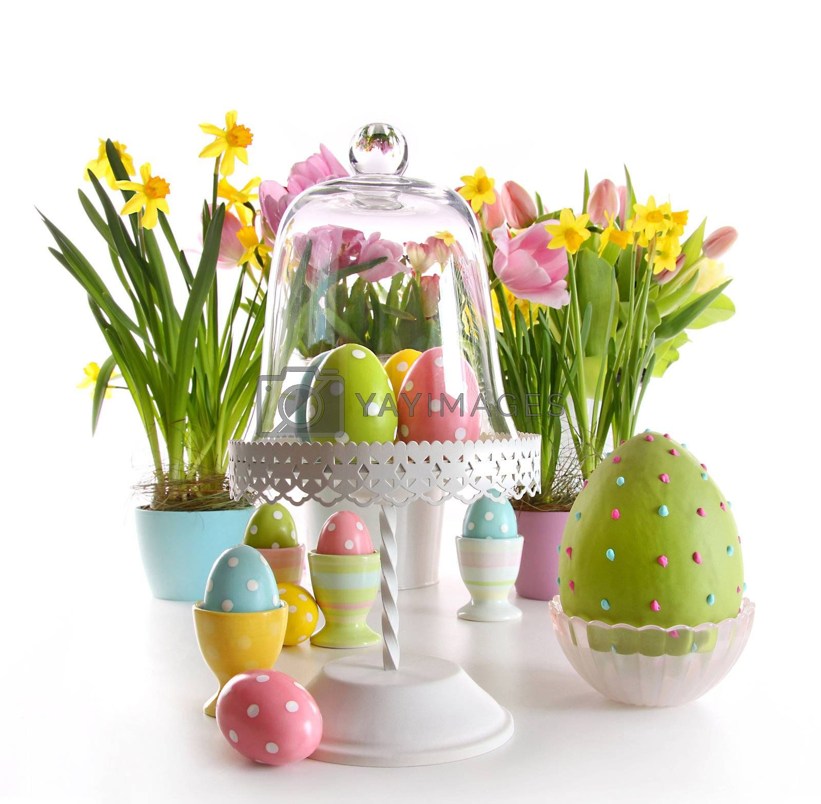 Easter eggs on cake stand with spring flowers on white