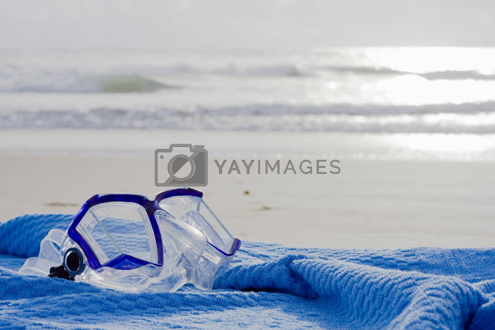 Diving mask on a blue towel on the beach