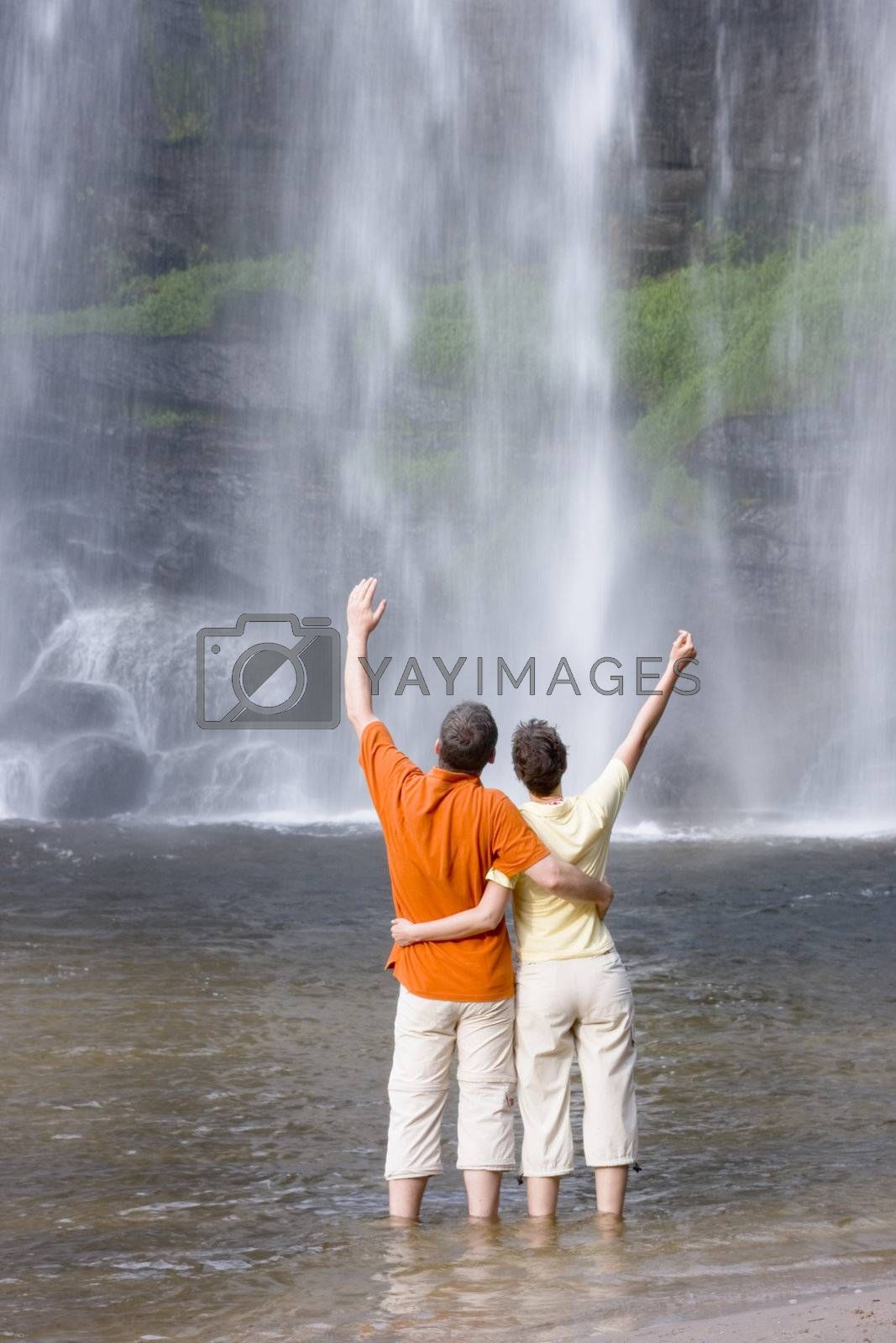 Couple with uplifted arms in front of a tropical waterfall in Brazil