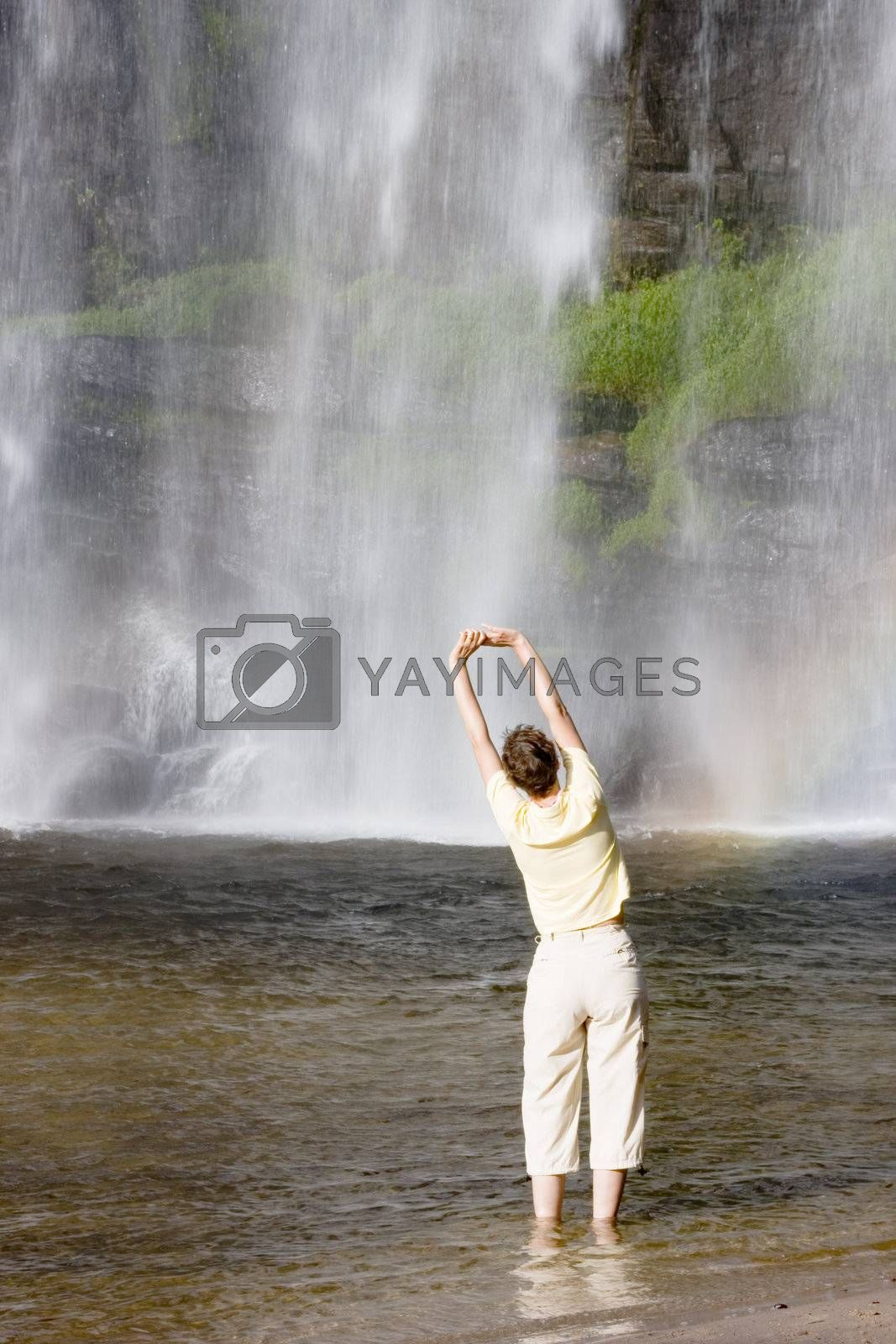 Woman doing gymnastics in front of a tropical waterfall