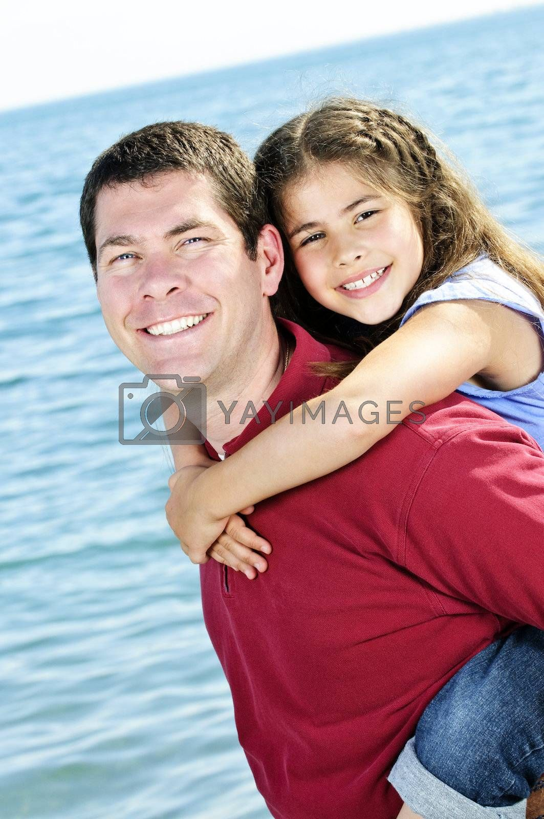 Portrait of father giving piggyback ride to daughter at seashore
