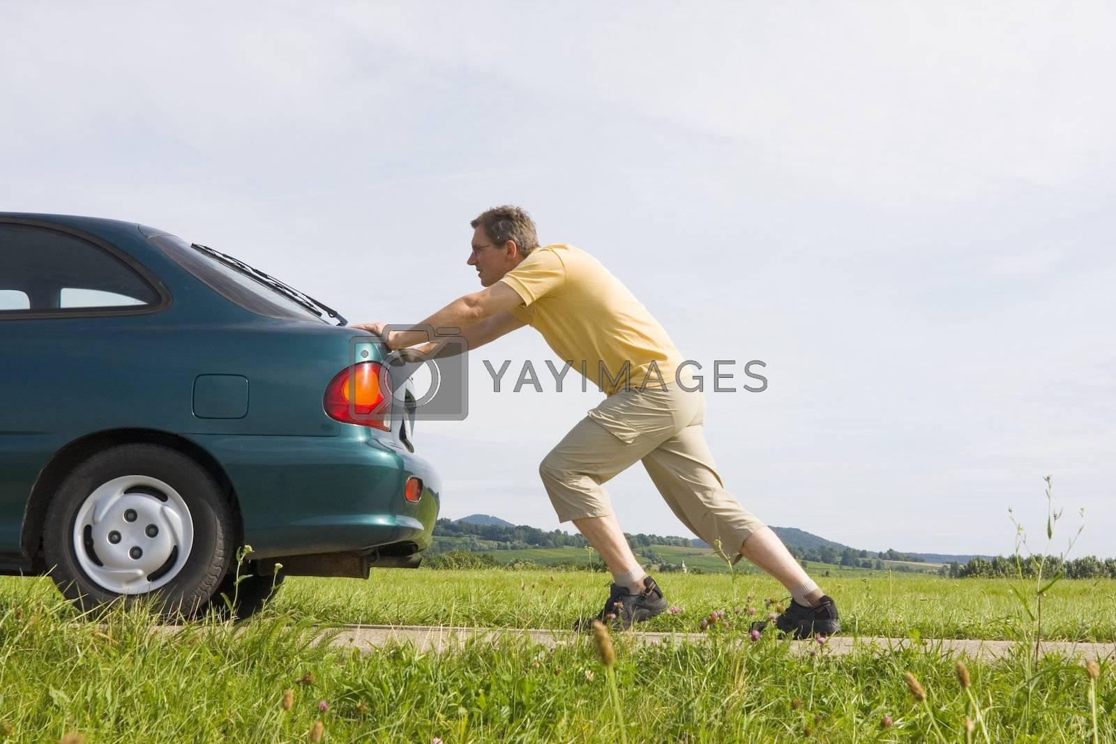 Royalty free image of Man pushing his car by ArtmannWitte