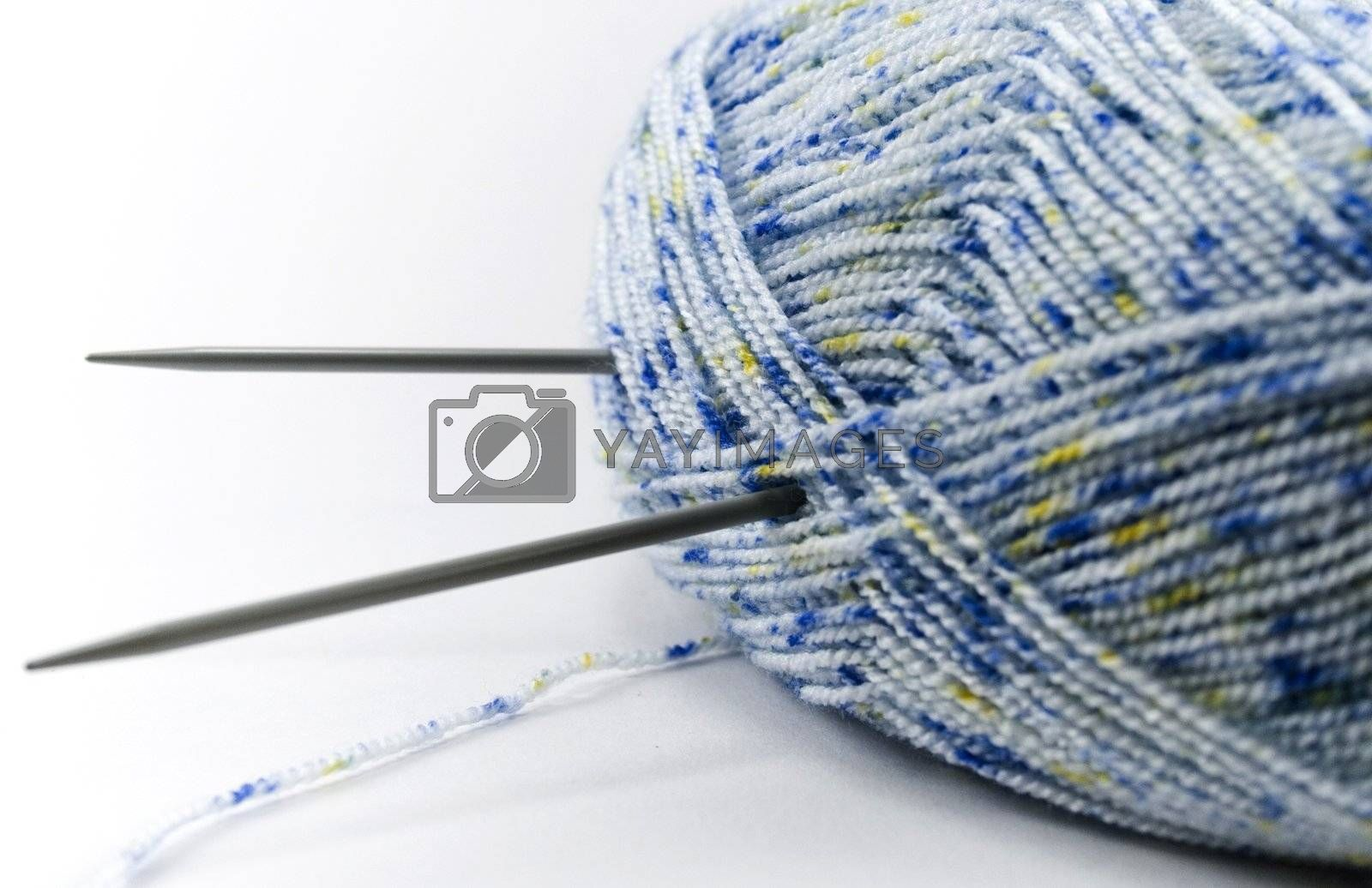Blue wool and needles over white