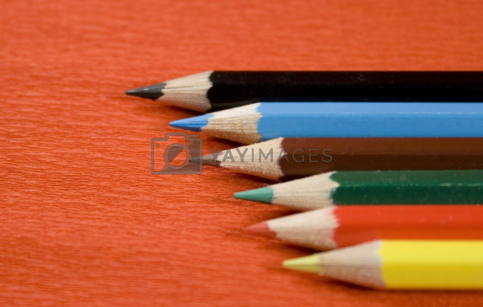 six coloured pencils over red background
