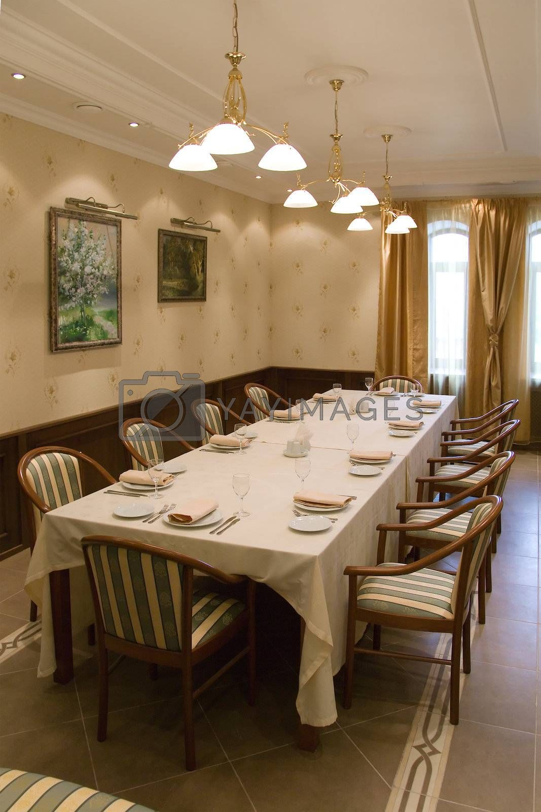 Table with chairs prepared for banquet in banquet-hall