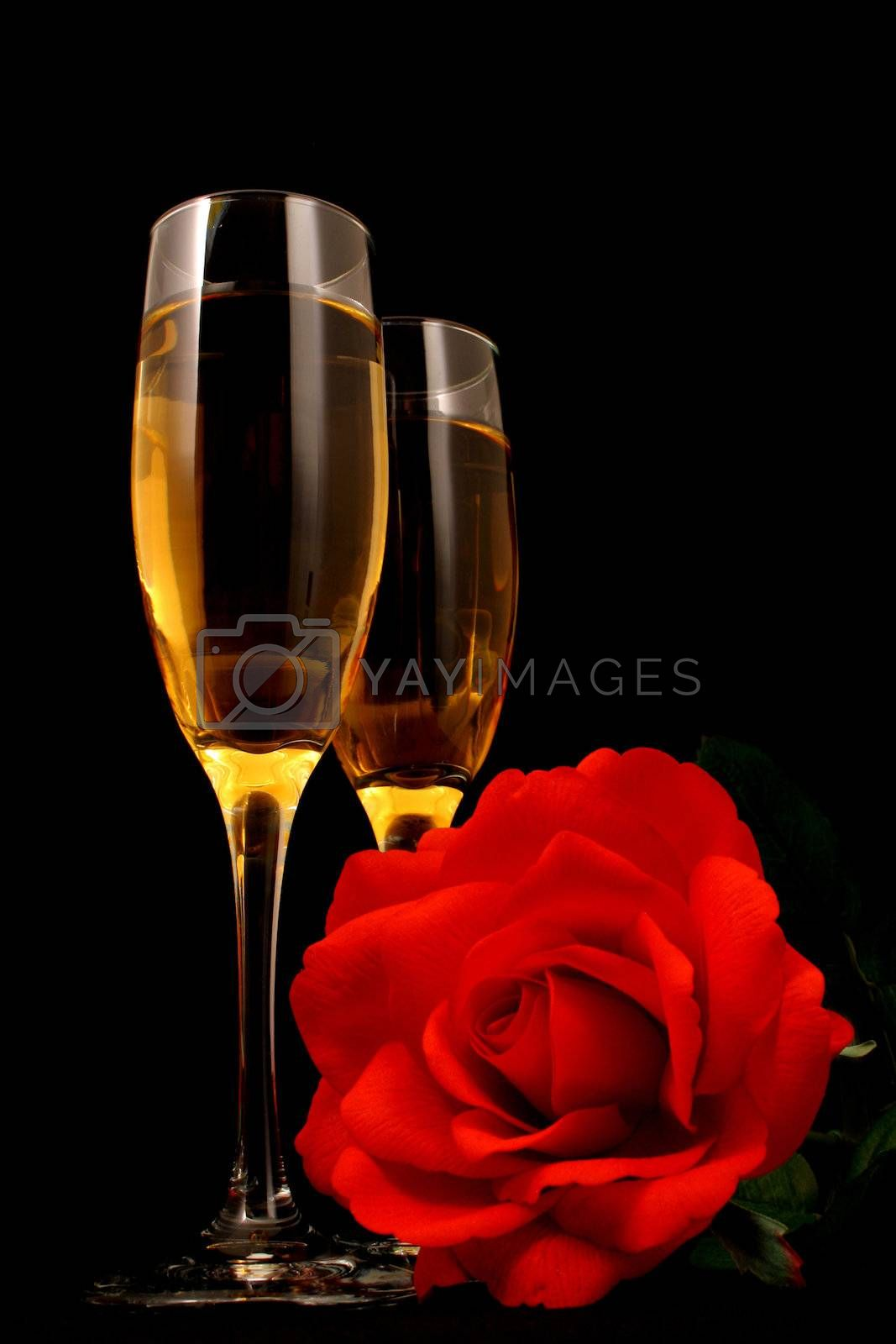 Wine in glasses with a rose all on a black background with mood lighting