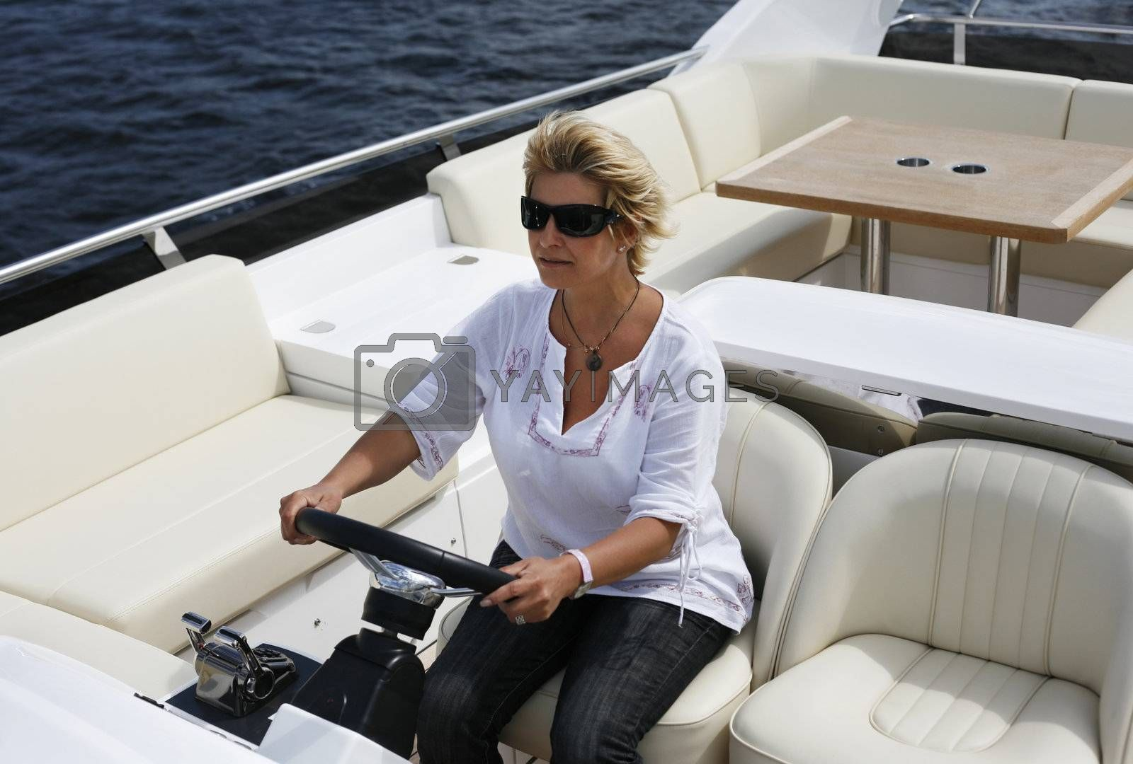 The adult woman behind a steering wheel of a yacht