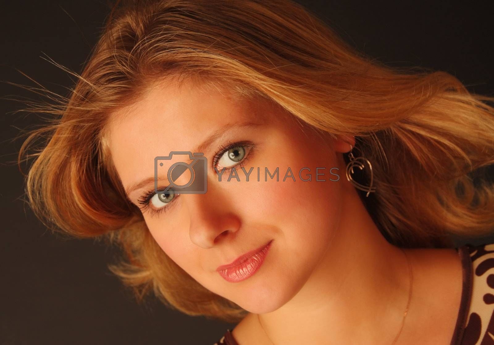 Head portrait of a pretty blond girl with wind blown hair