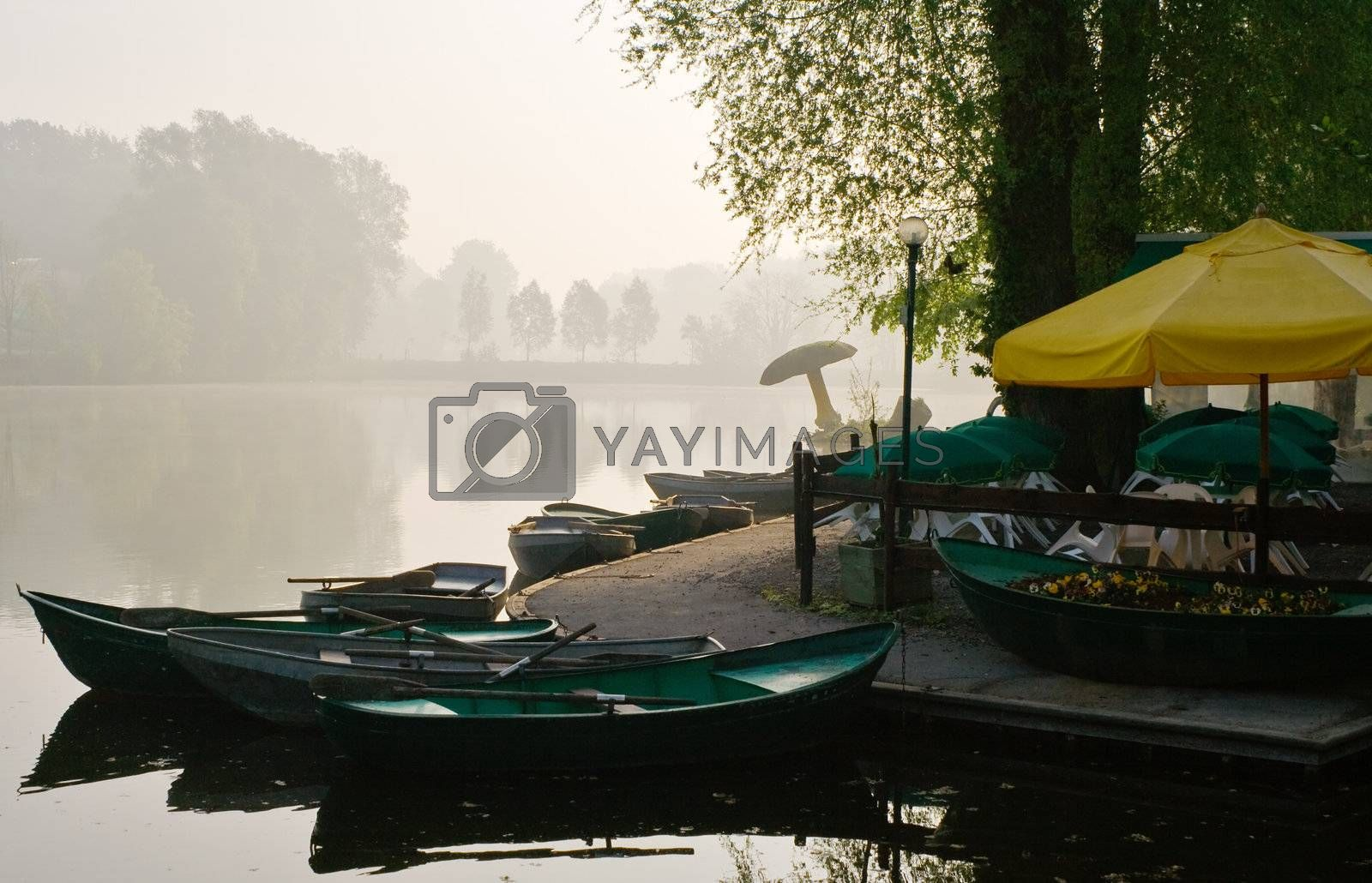Rowing boats on the lakeside in a misty morning
