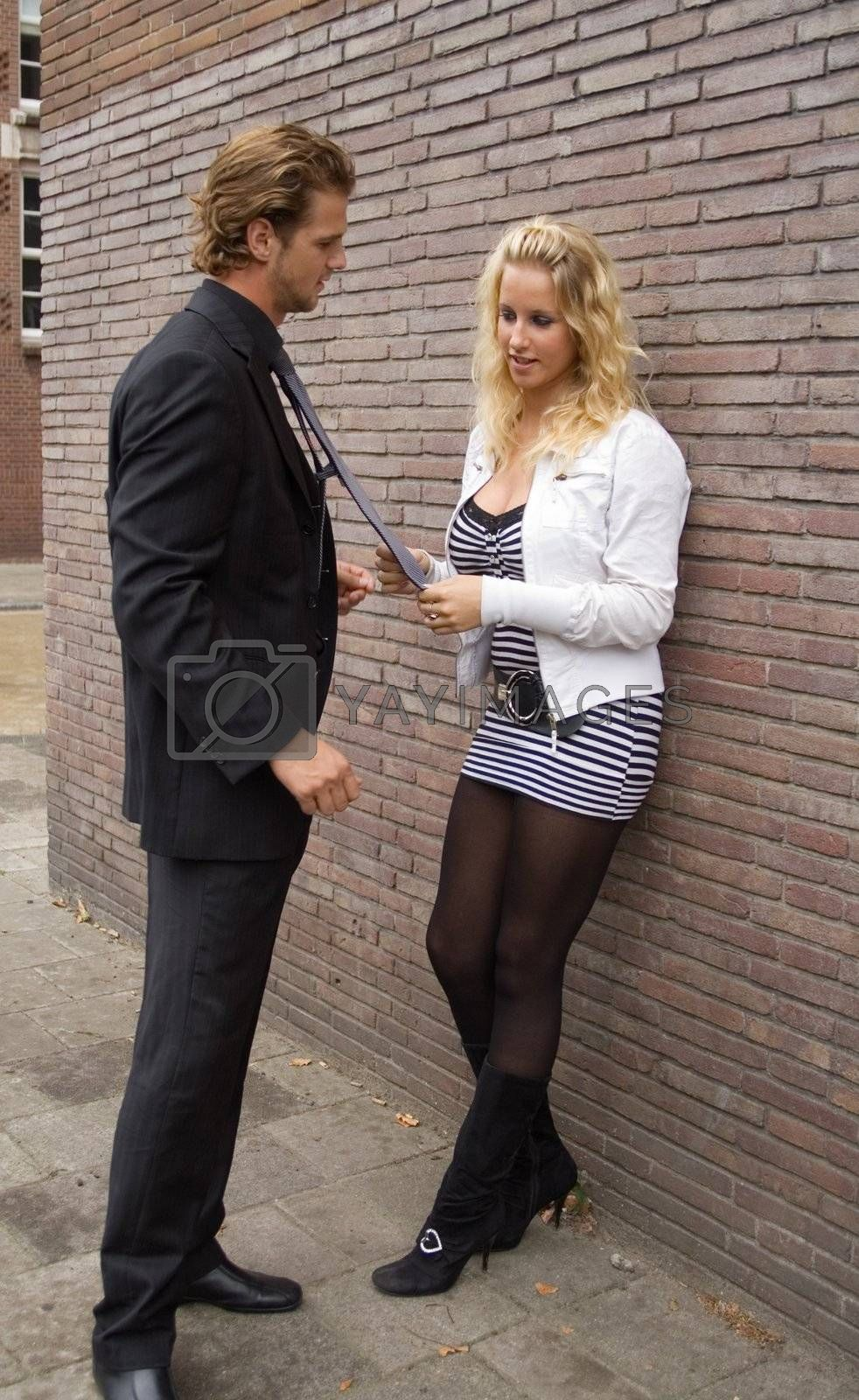 couple standing next to a brick wall