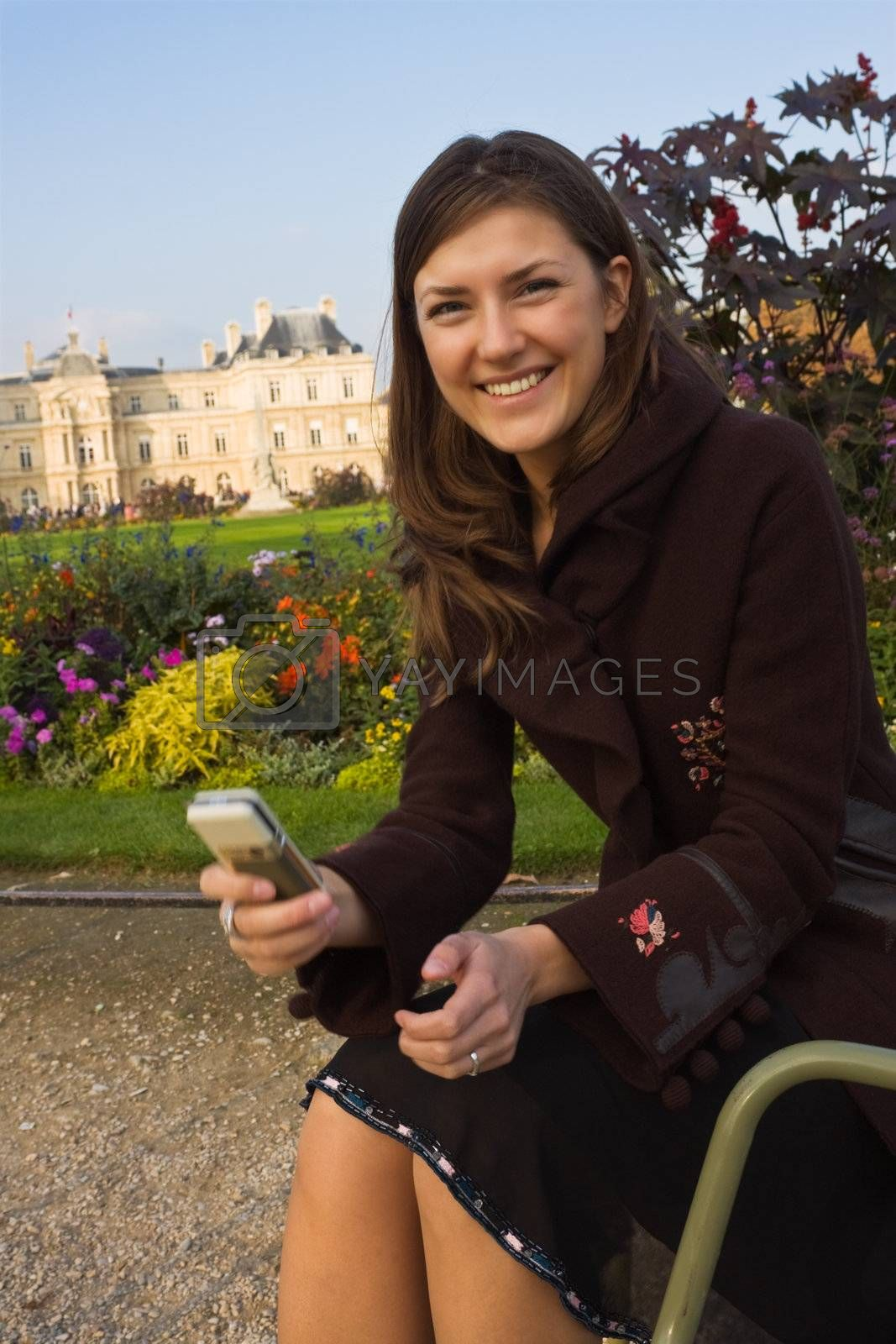 laughting girl with her mobile phone, sitting on metal chair in a park