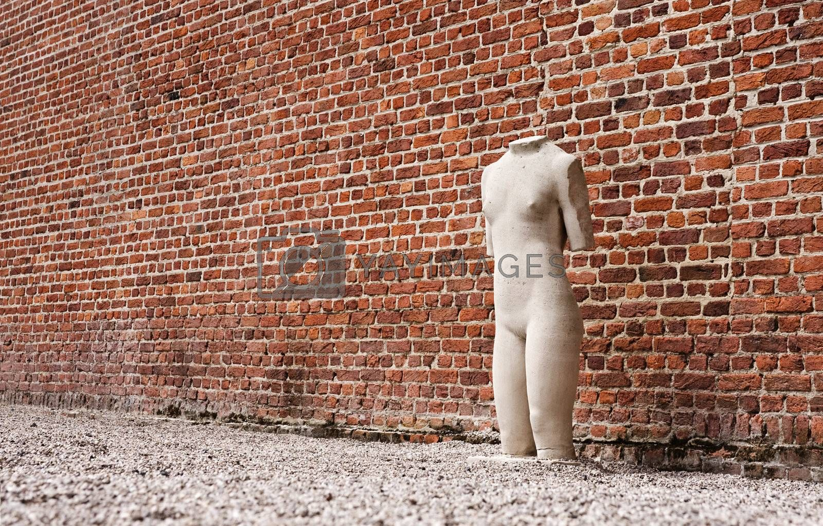 Lonely sculpture standing next to red-brick wall