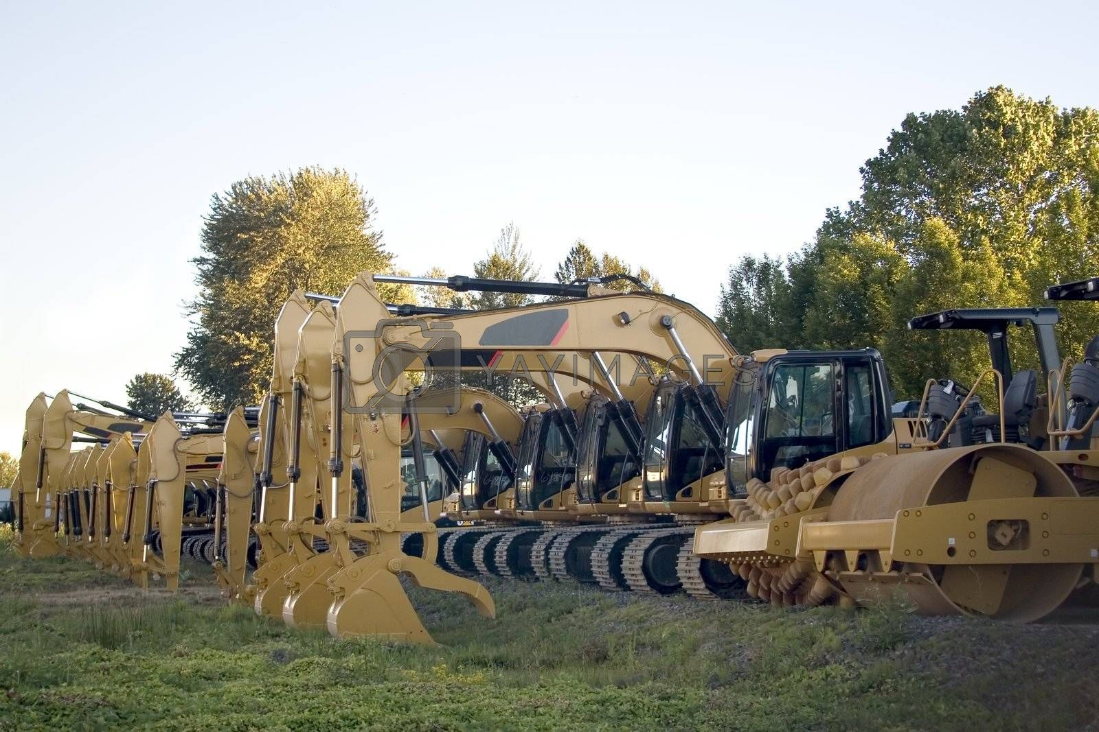New steamrollers, bulldozers and front-end loaders in a row on the sales lot.