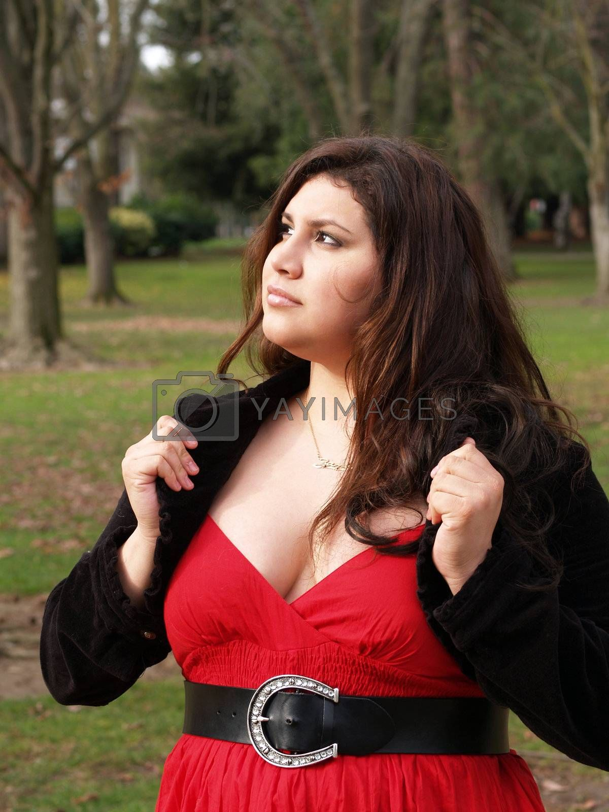 plus-size woman outdoors in jacket and red dress