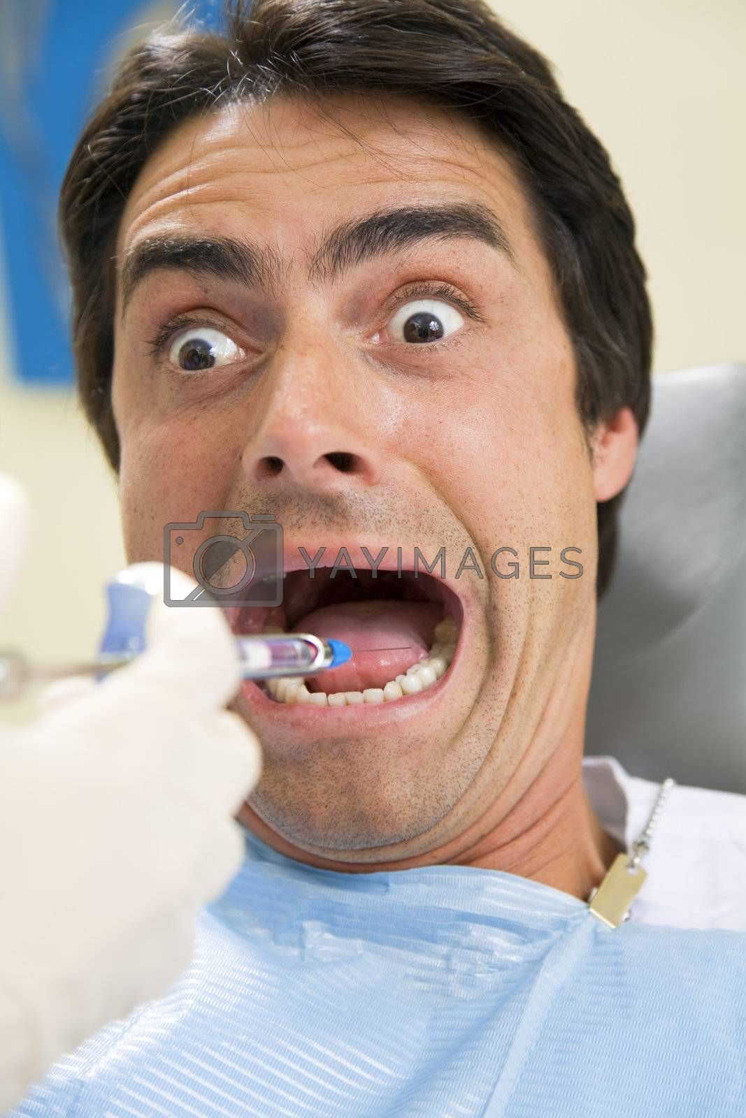 dentist holding a syringe and anesthetizing his terrified patient.