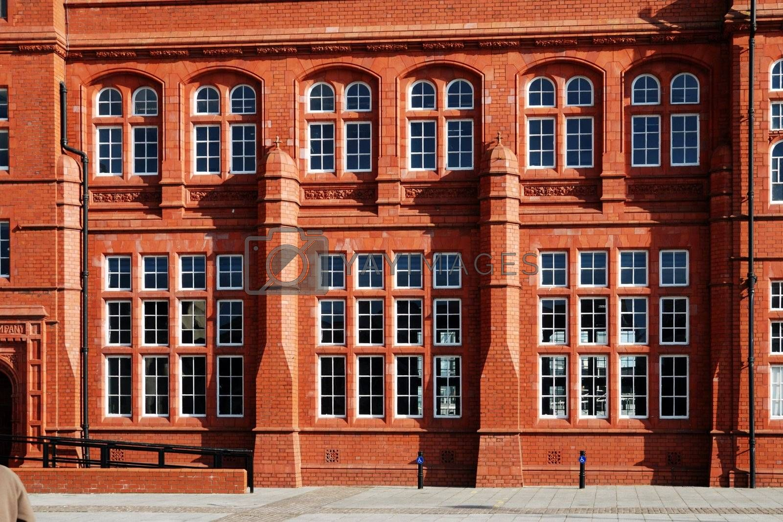 wall of red historical building in cardiff bay with windows