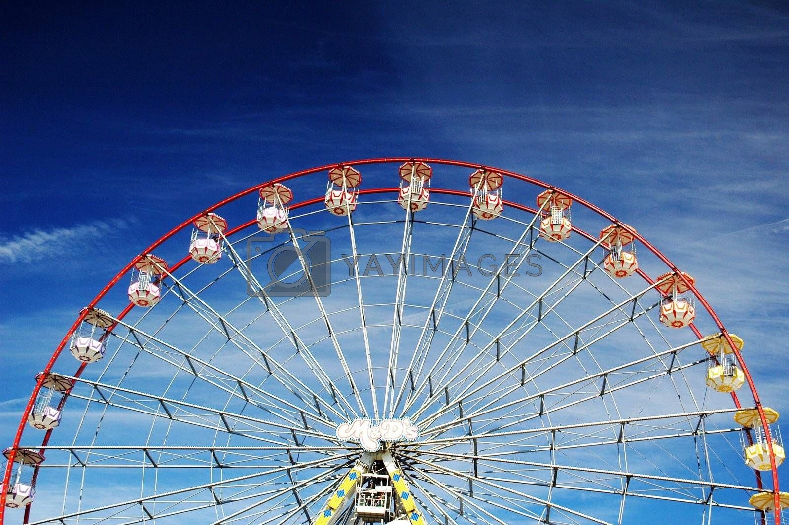 big wheel in cardiff bay in nice summer day with blue sky covered by clouds