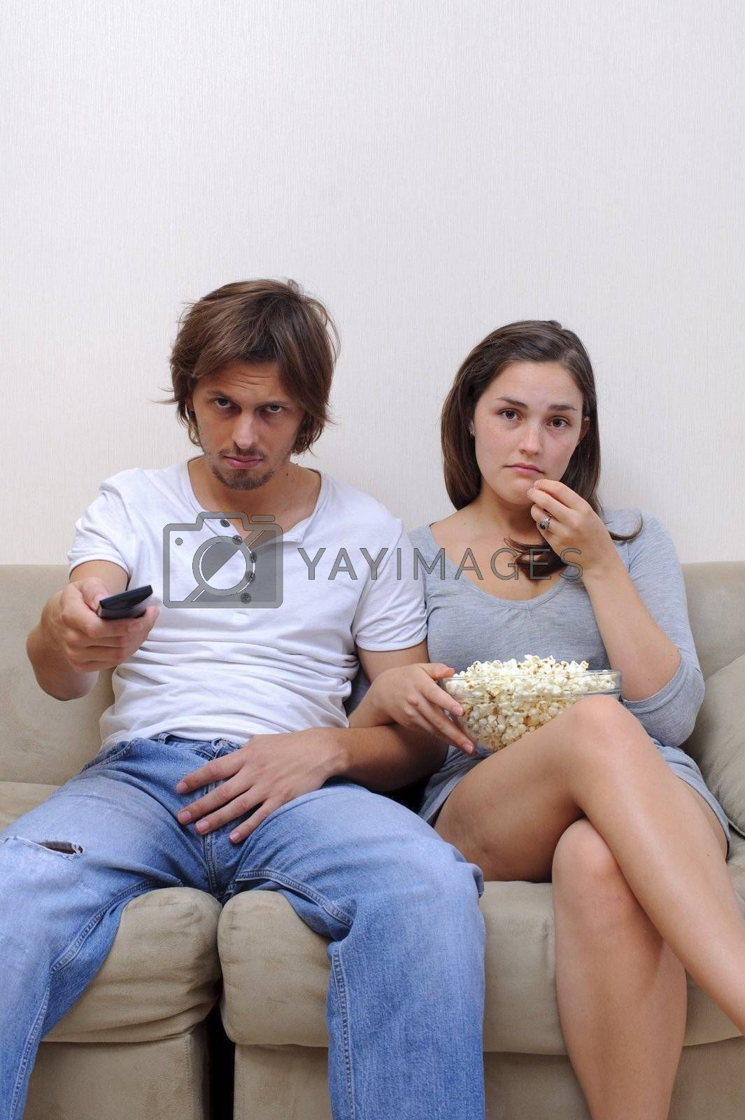 Couple watch a movie at home with popcorn