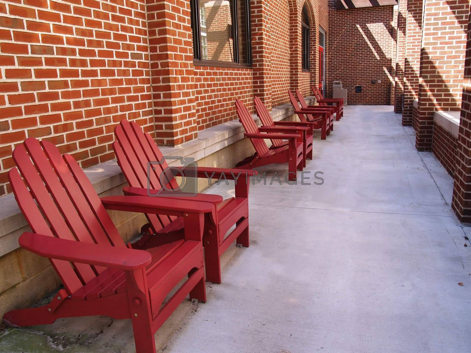 row of red adirondack chairs by a brick building