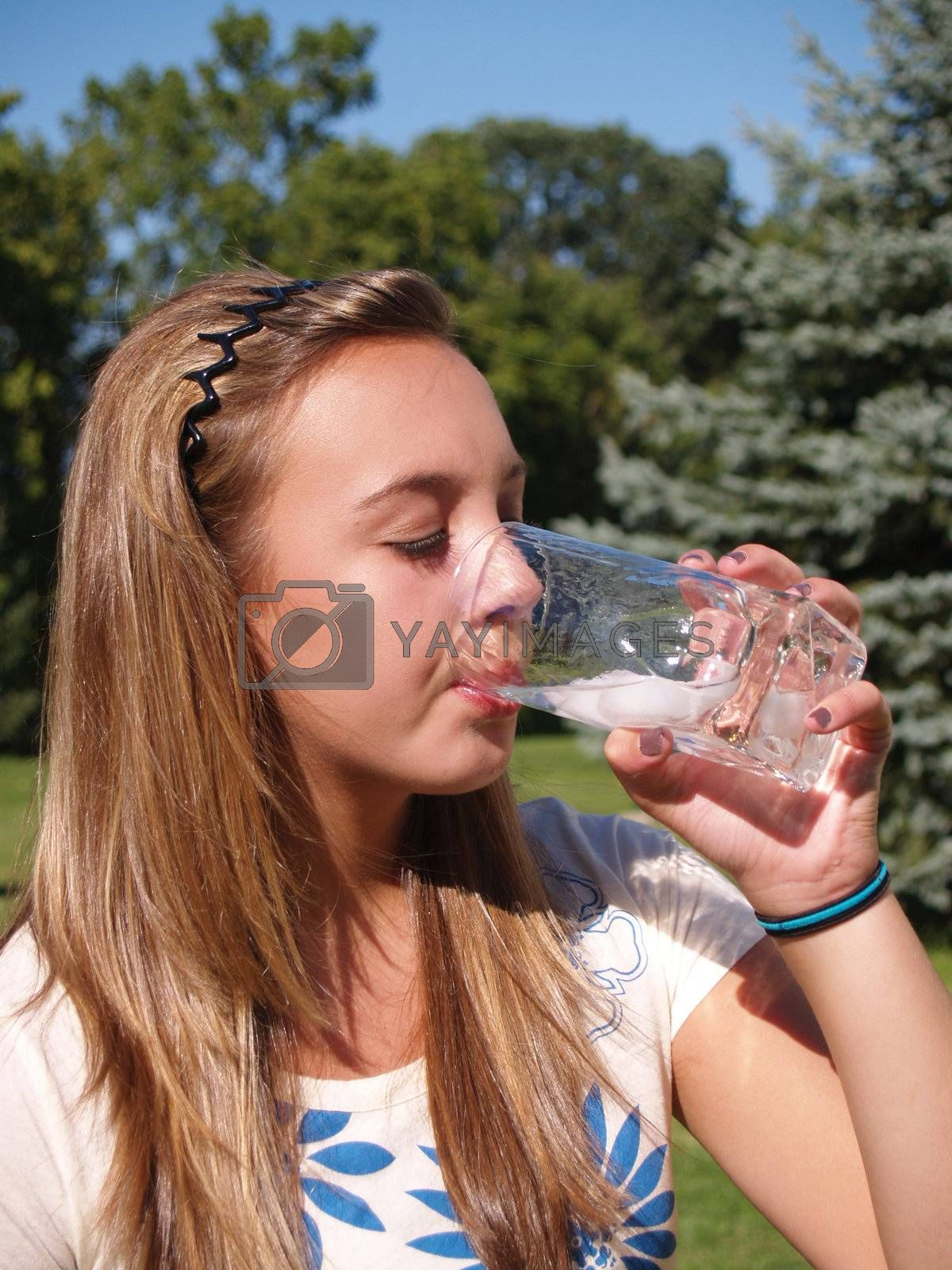 closeup of a teenage girl drinking water from a glass