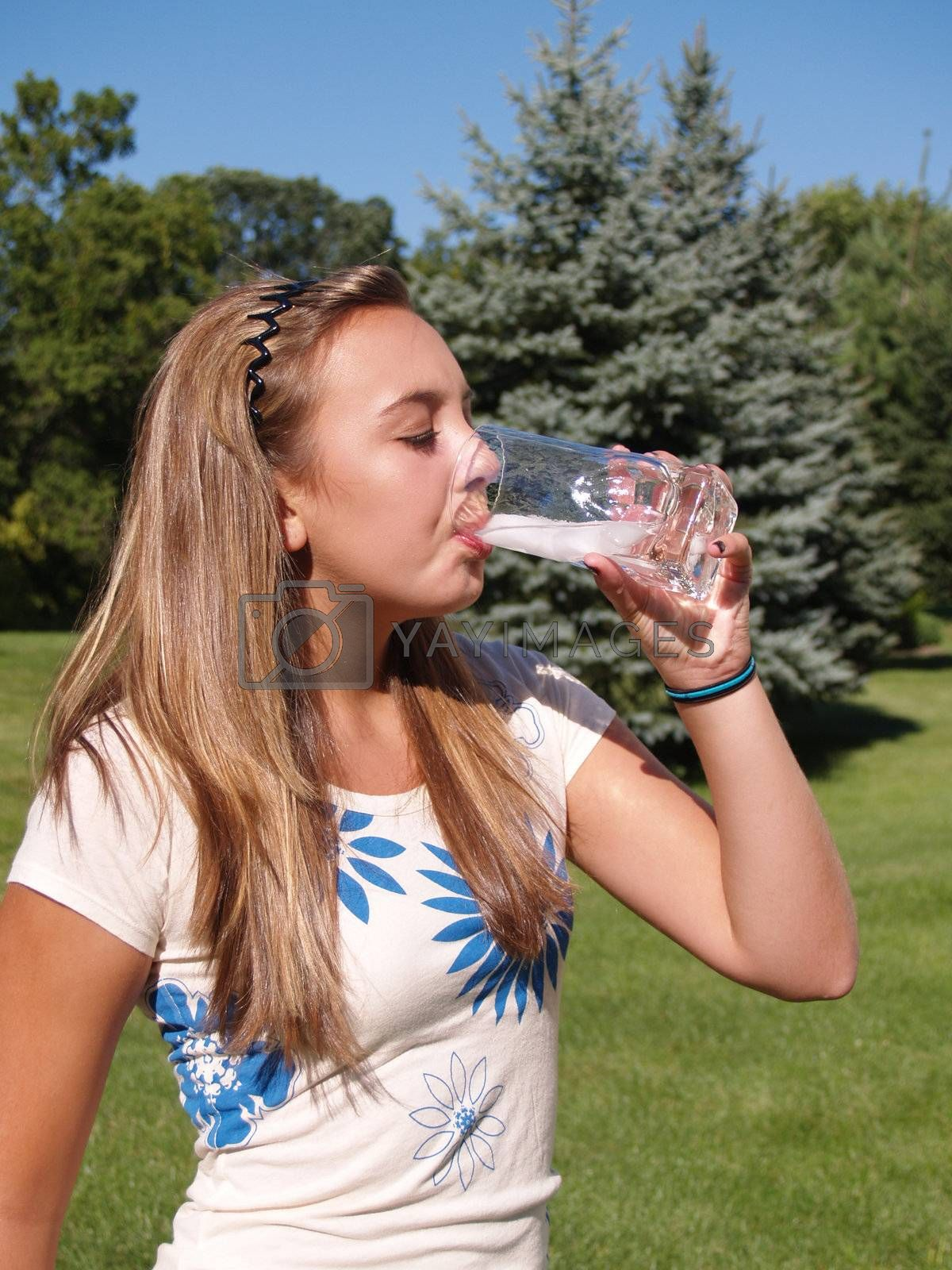 teenage girl drinking water in a glass