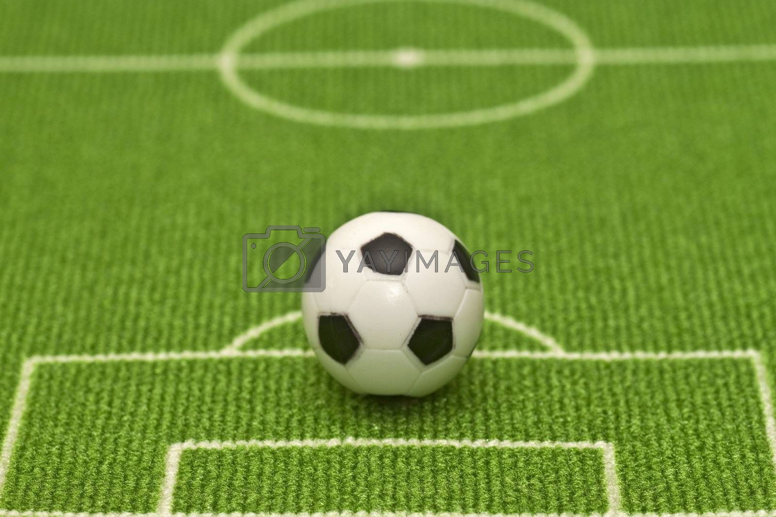 Symbol photo toy soccer ball on a football field. Shot in studio.
