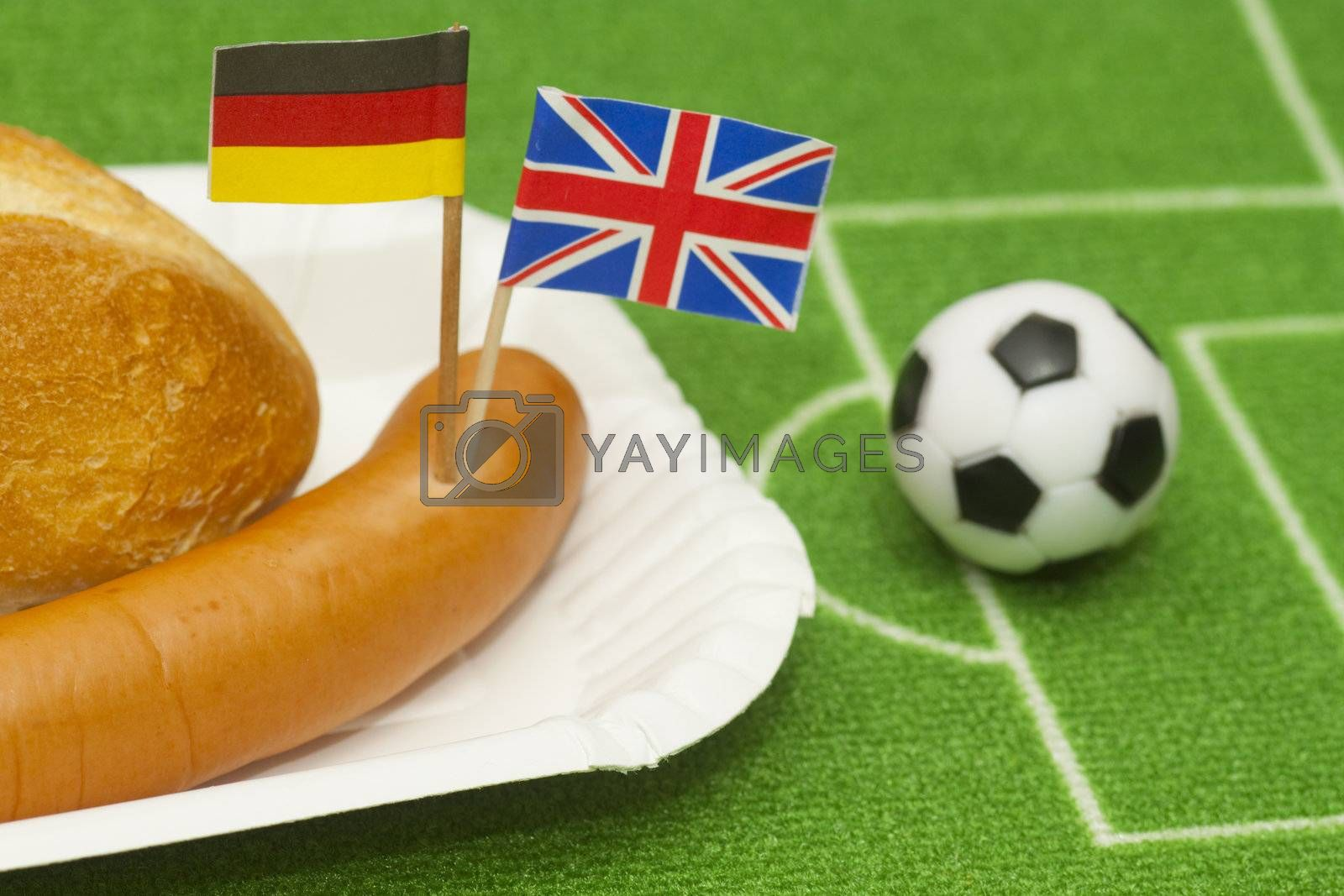 Sausage with roll on a football field background with soccer ball