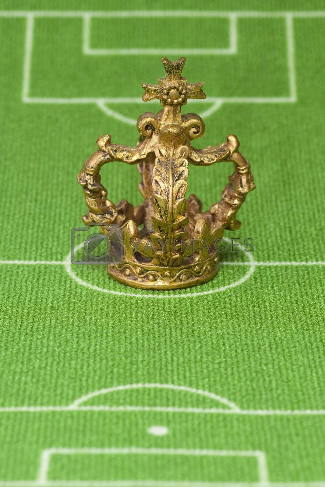 Symbol photo - crown on a soccer field. Shot in studio.