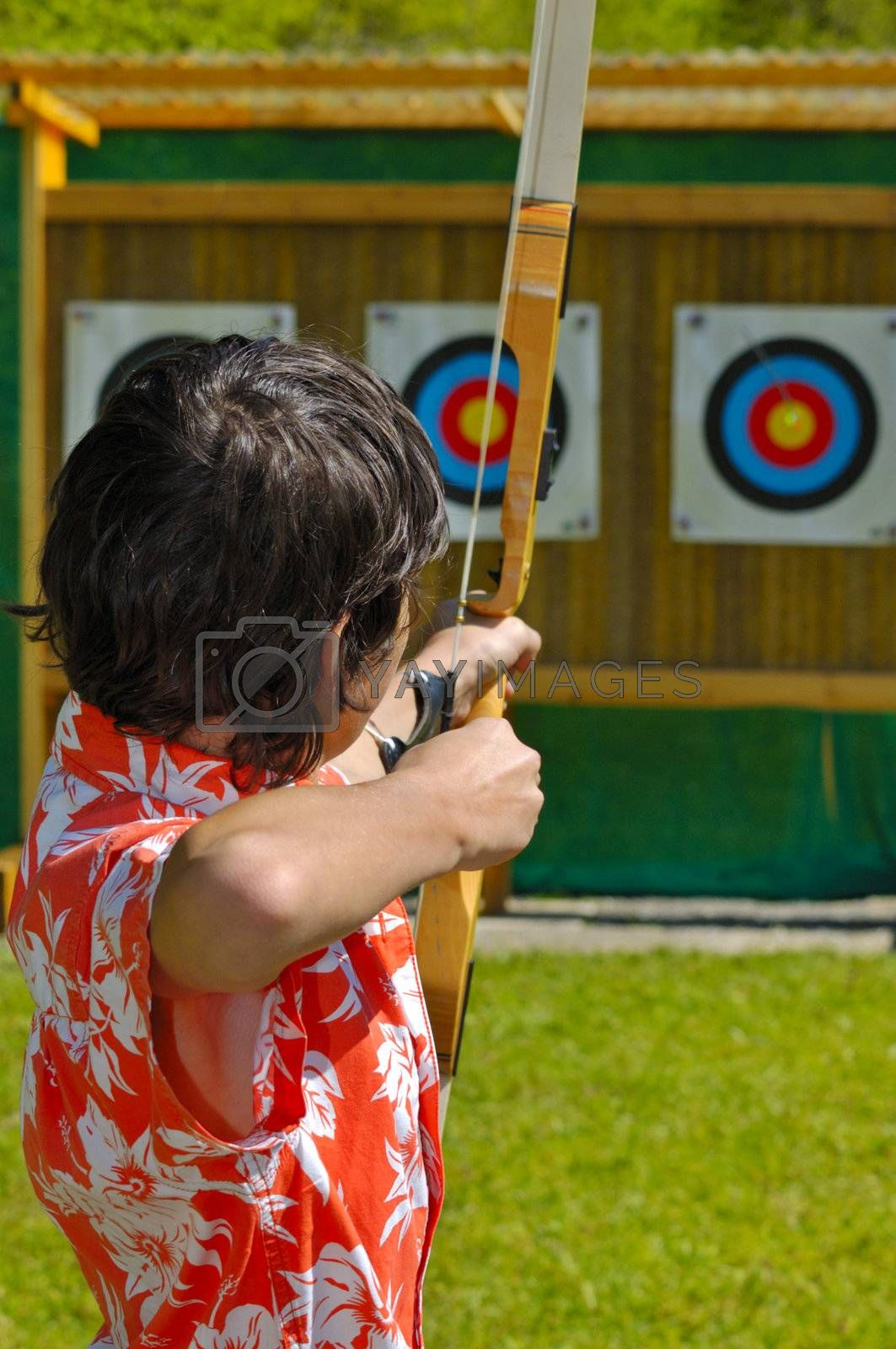 An archer aims at the bullseye of a distant target. Focus on the archer's head. The arrow can just be seen, out of focus, in the bullseye.