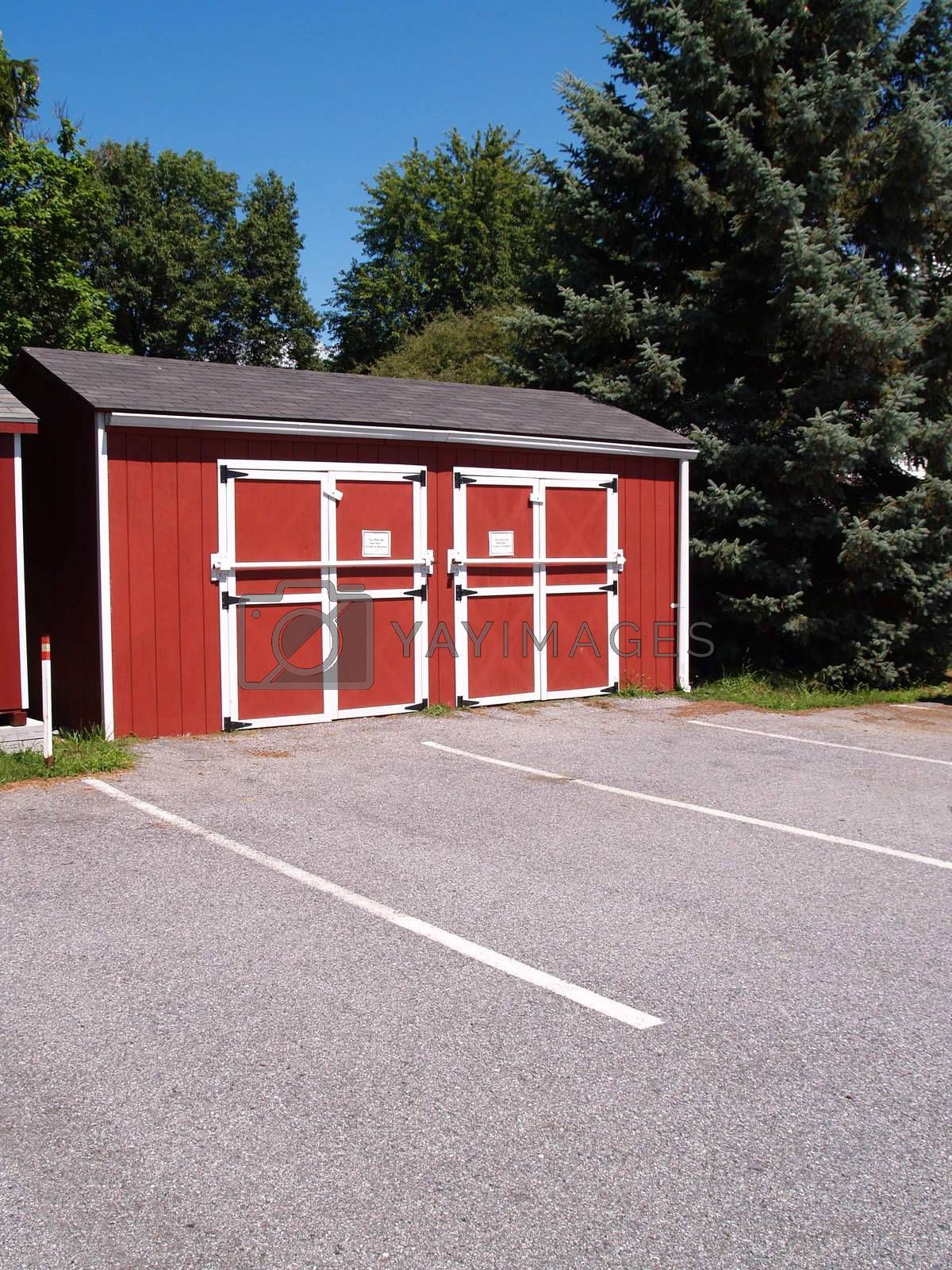 one red utility shed for storage near a parking lot