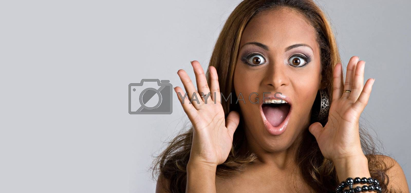 An amazed and shocked woman isolated over a silver background.  Lots of copy space for your text.