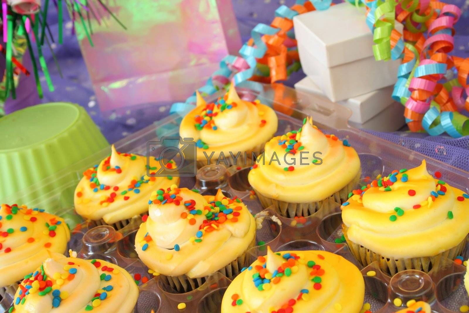 A grouping of beautifully colored cup cakes with sprinkles and party supplies.  Used a shallow DOF and selective focus.