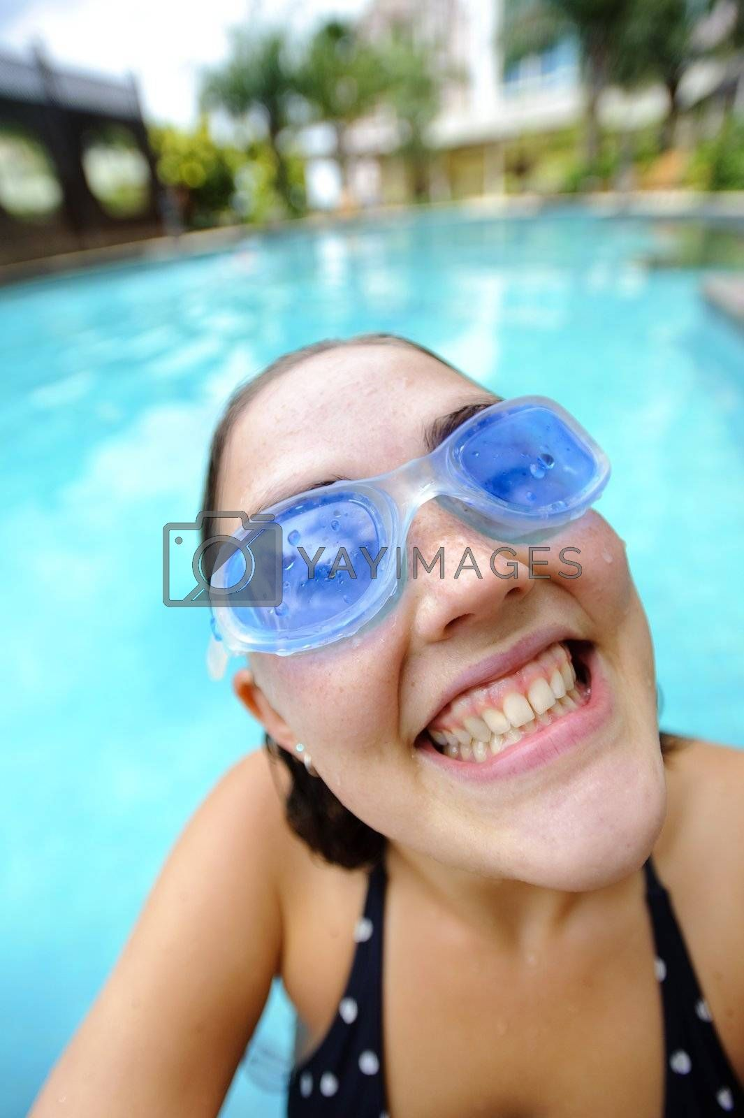 Woman is happy and smiles at the hotel pool