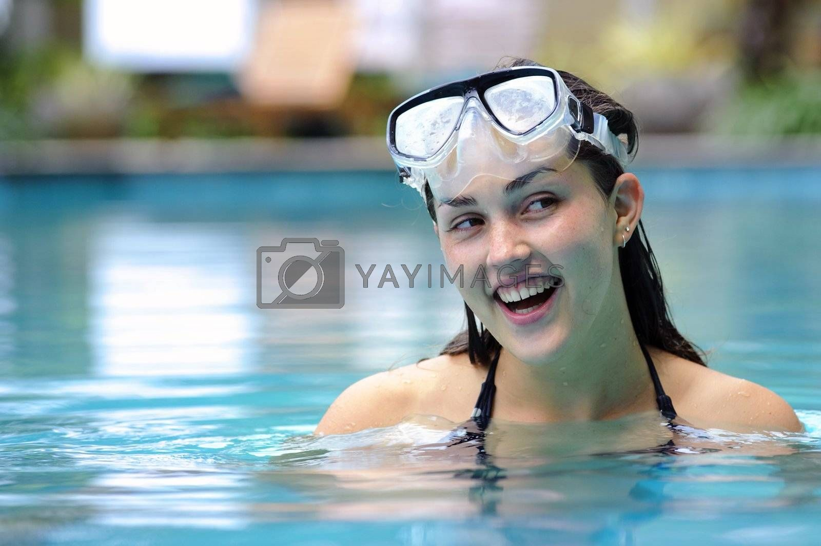 Pretty girl plays in the pool with her scuba mask