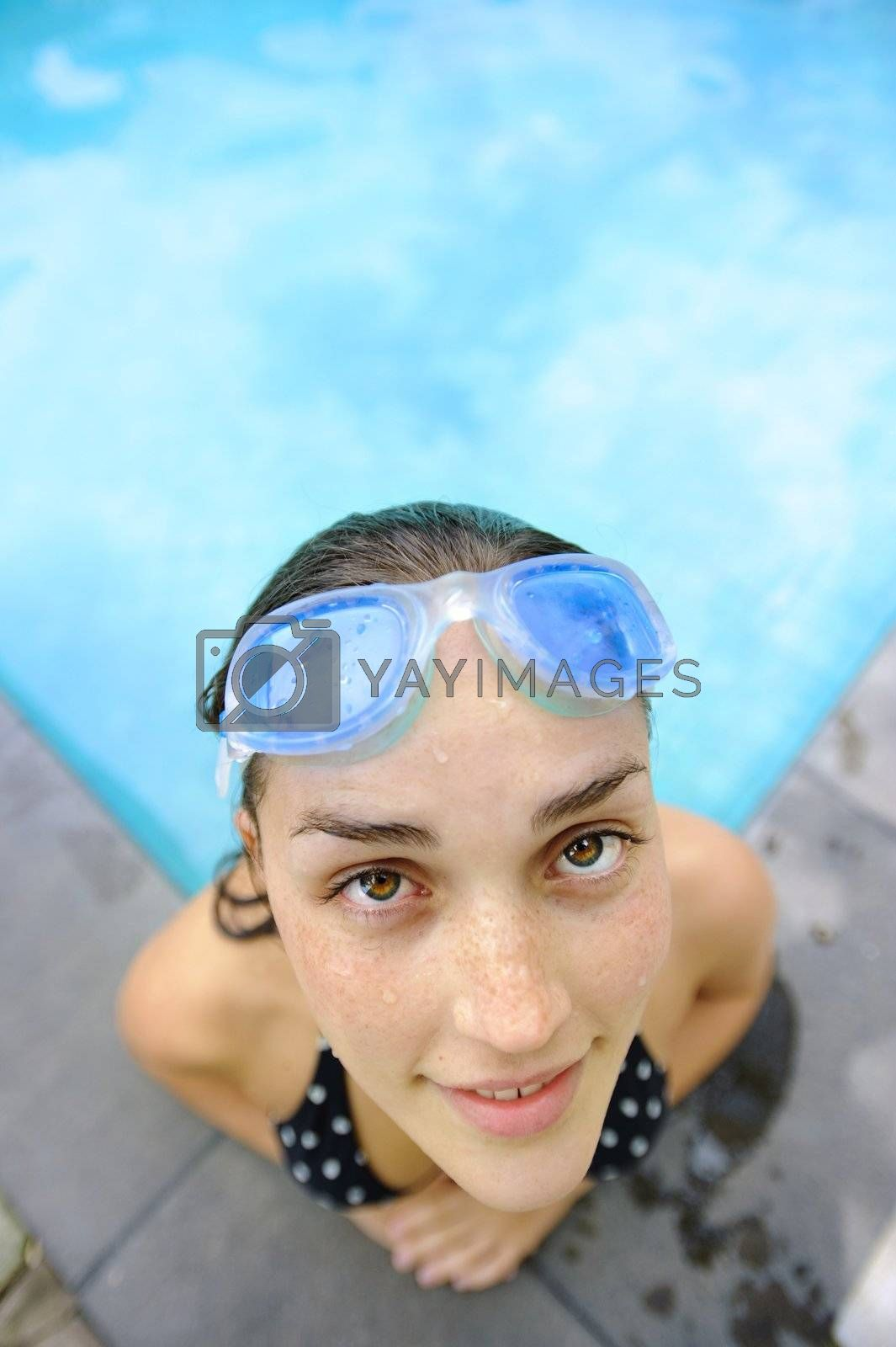 Girl looks up toward camera while in the pool