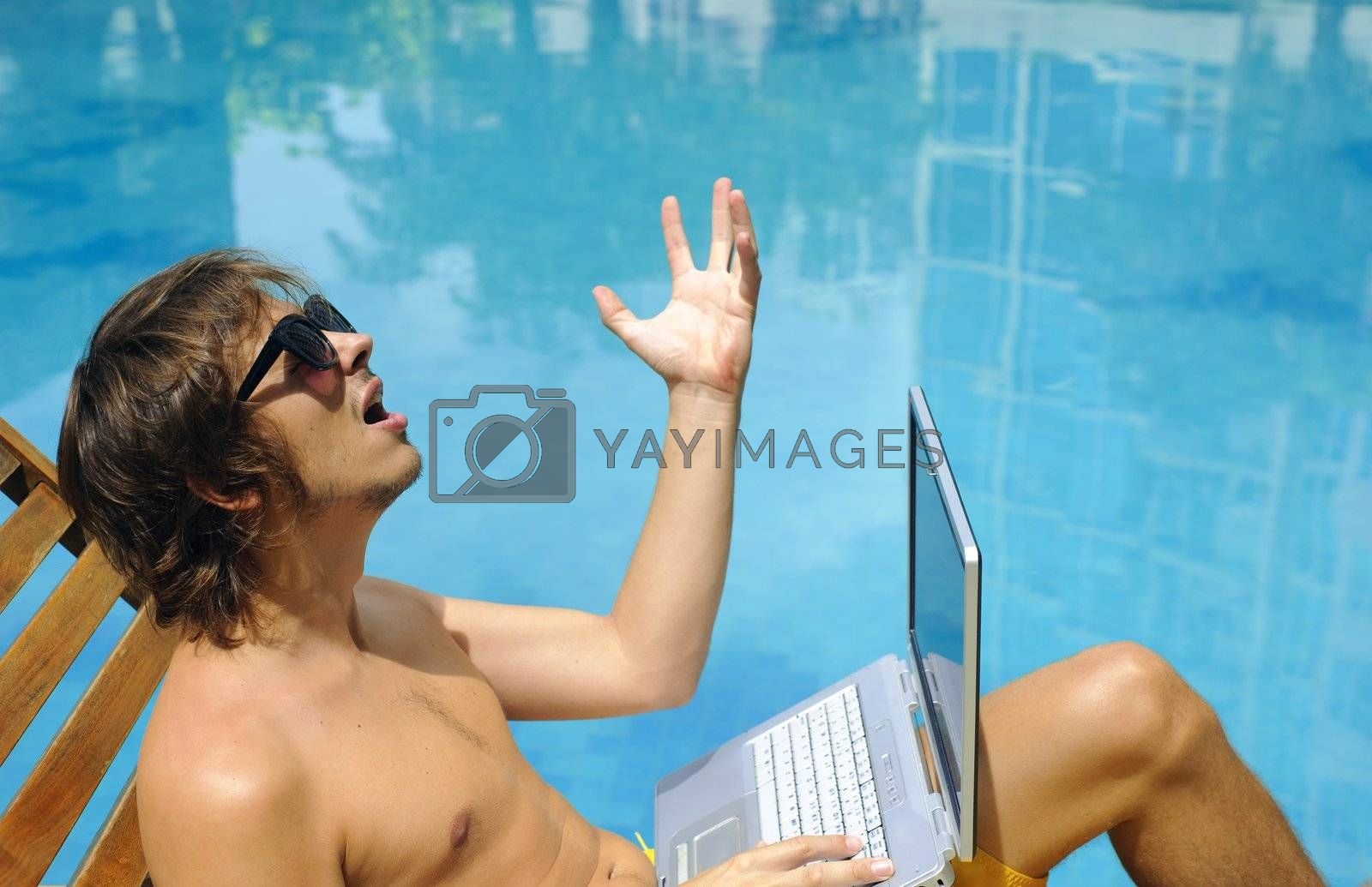 Man takes his laptop to the pool with him