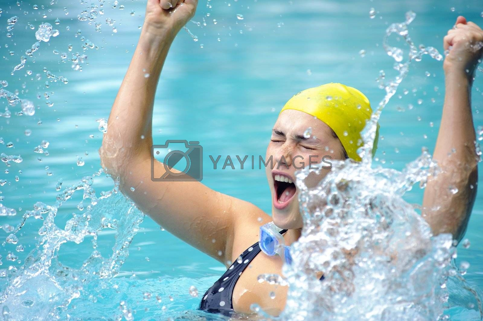 Pretty swimmer is happy and splashes in the water