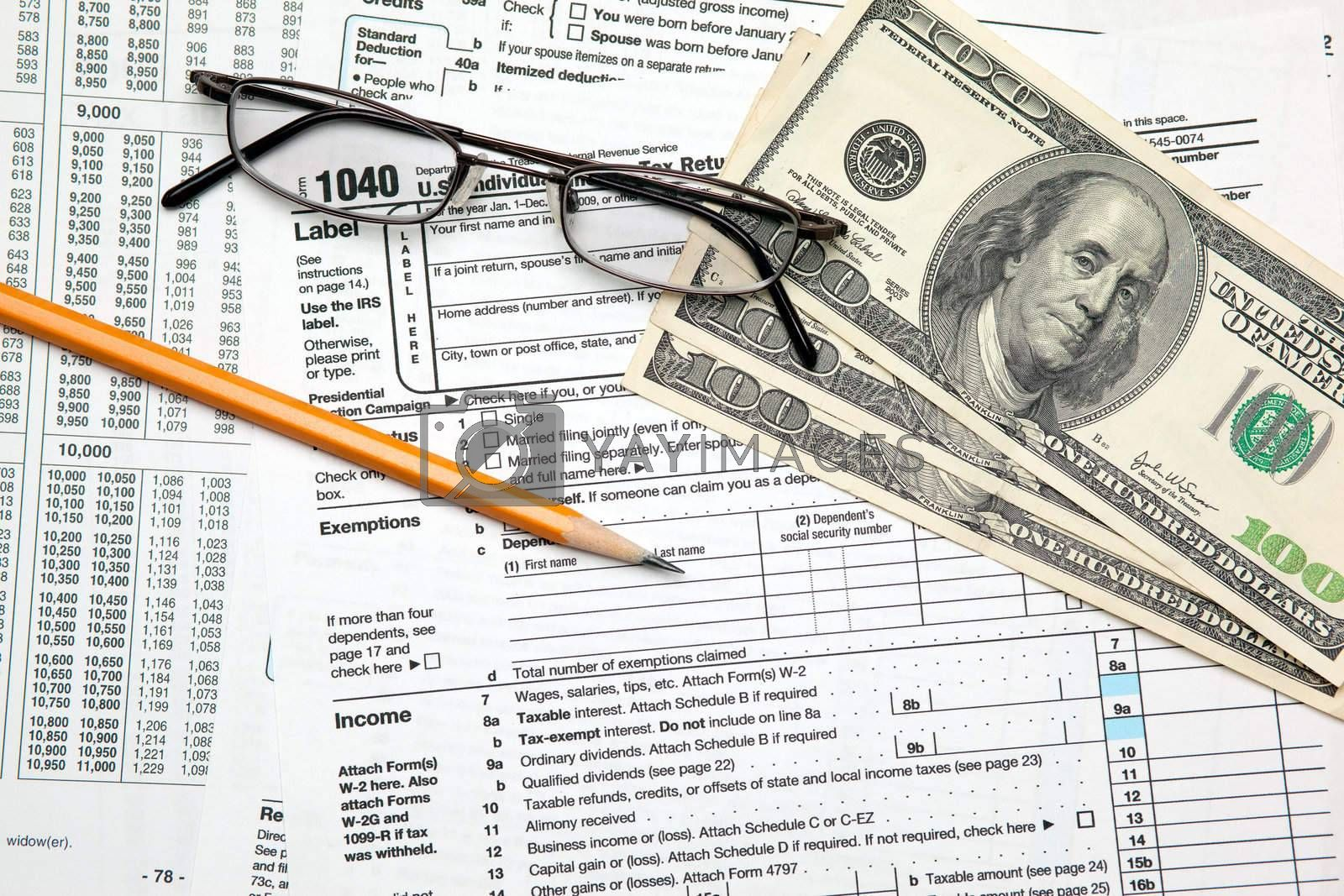 Tax time - Closeup of U.S. 1040 tax return with pencil and glass by svanblar