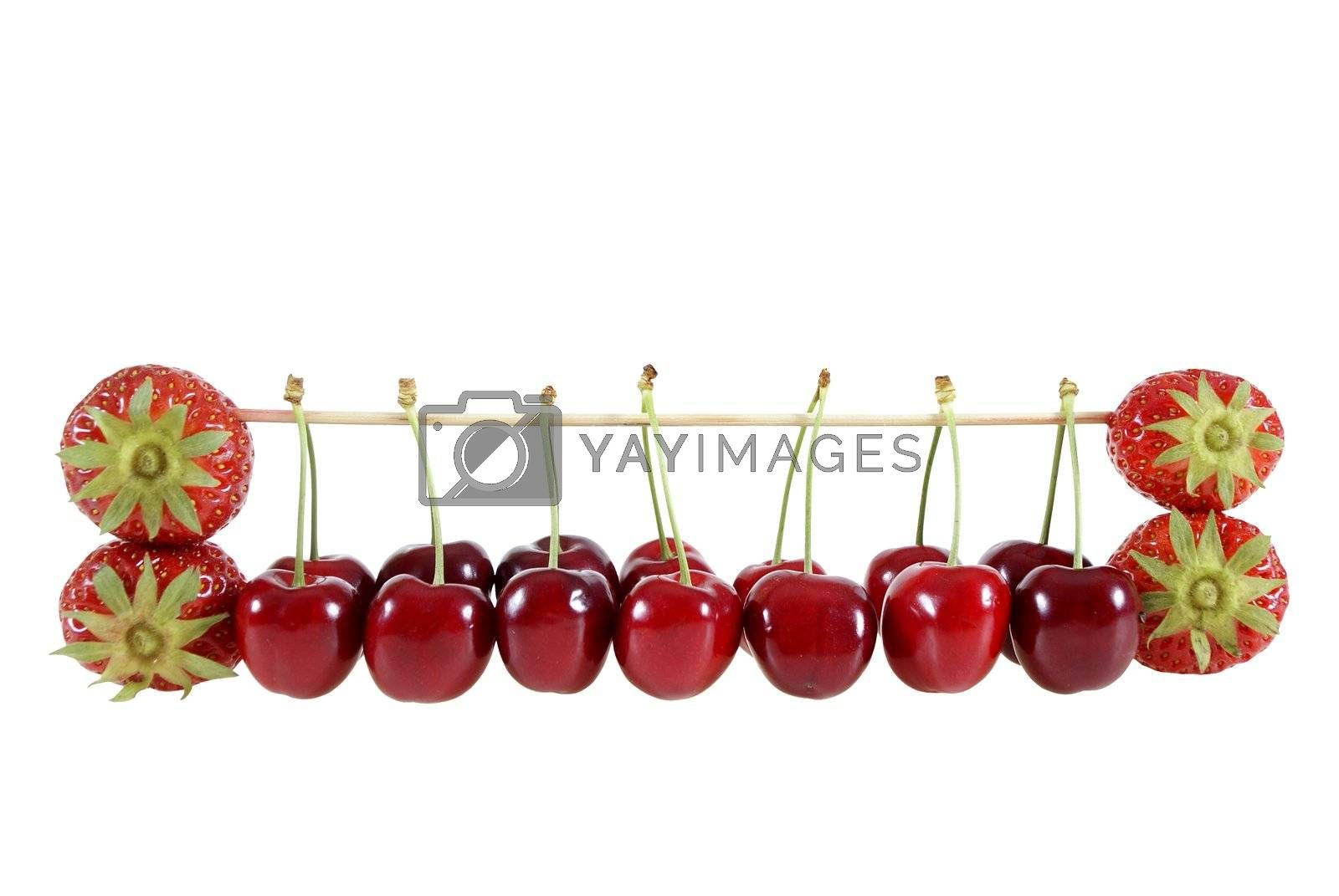 strawberries and cherries suspended on a stick isolated on the white background