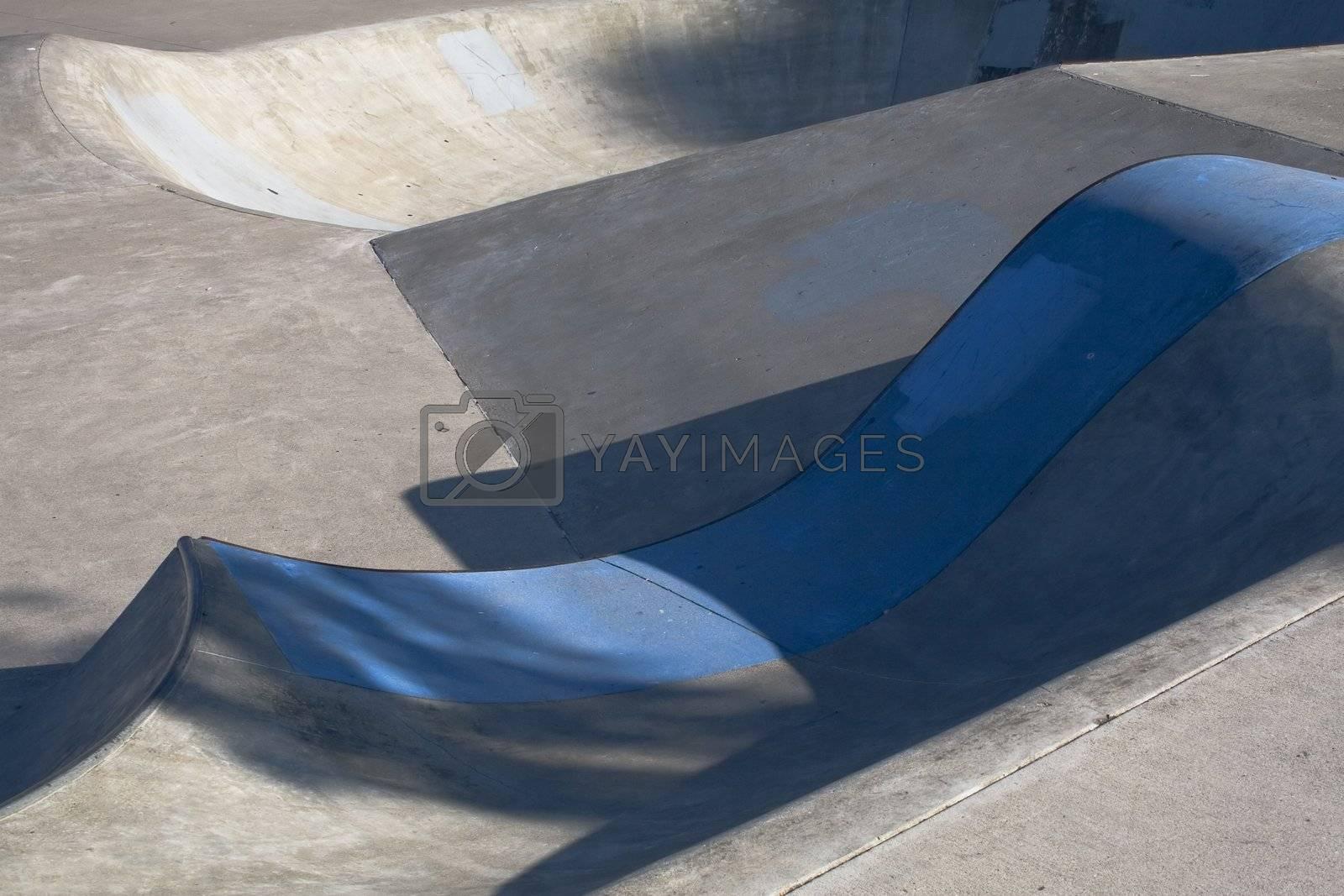 A skateboard park bowl with a blue painted concrete lip.