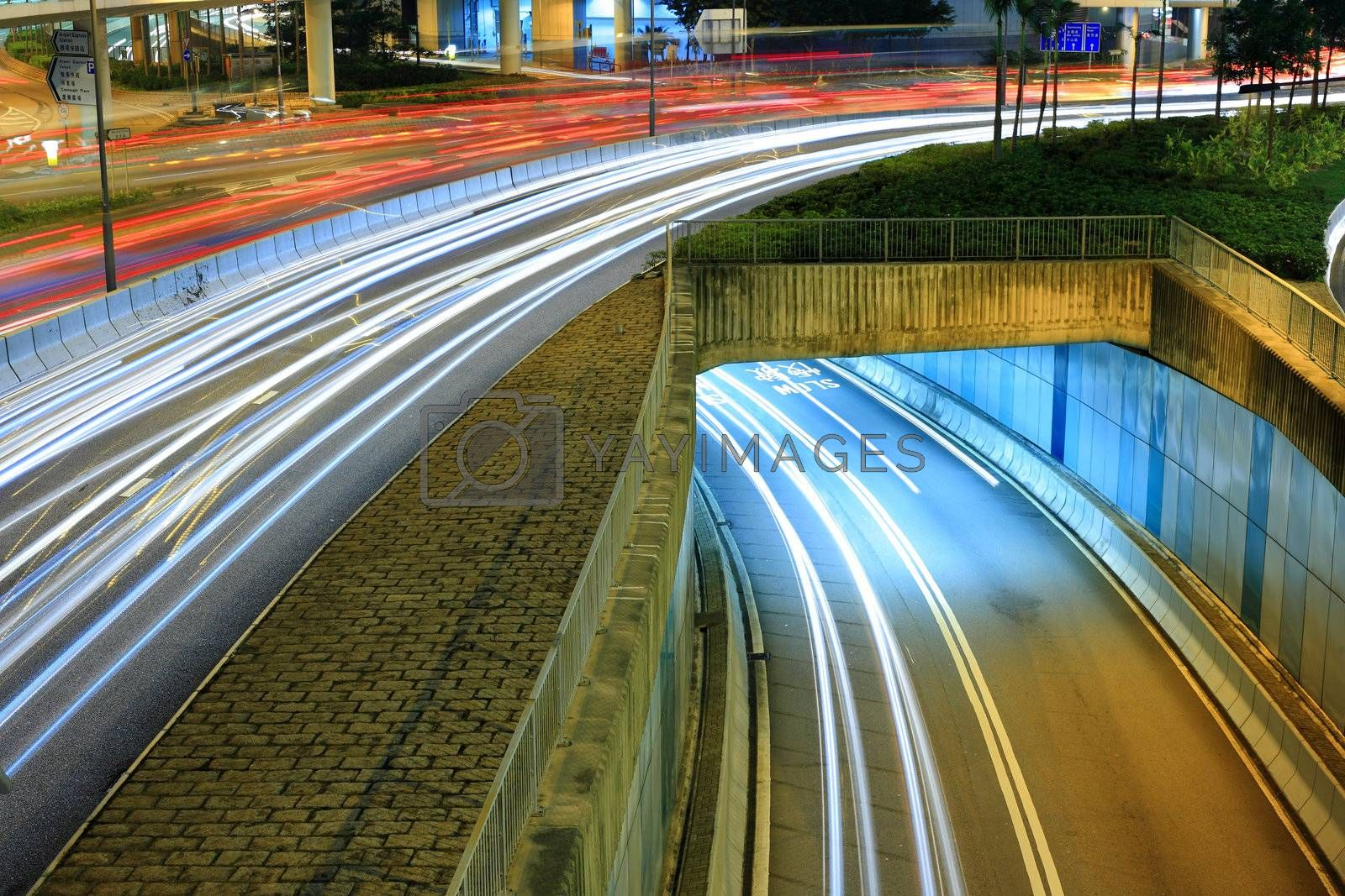 Royalty free image of Highway in city at night with trails of car lights by leungchopan