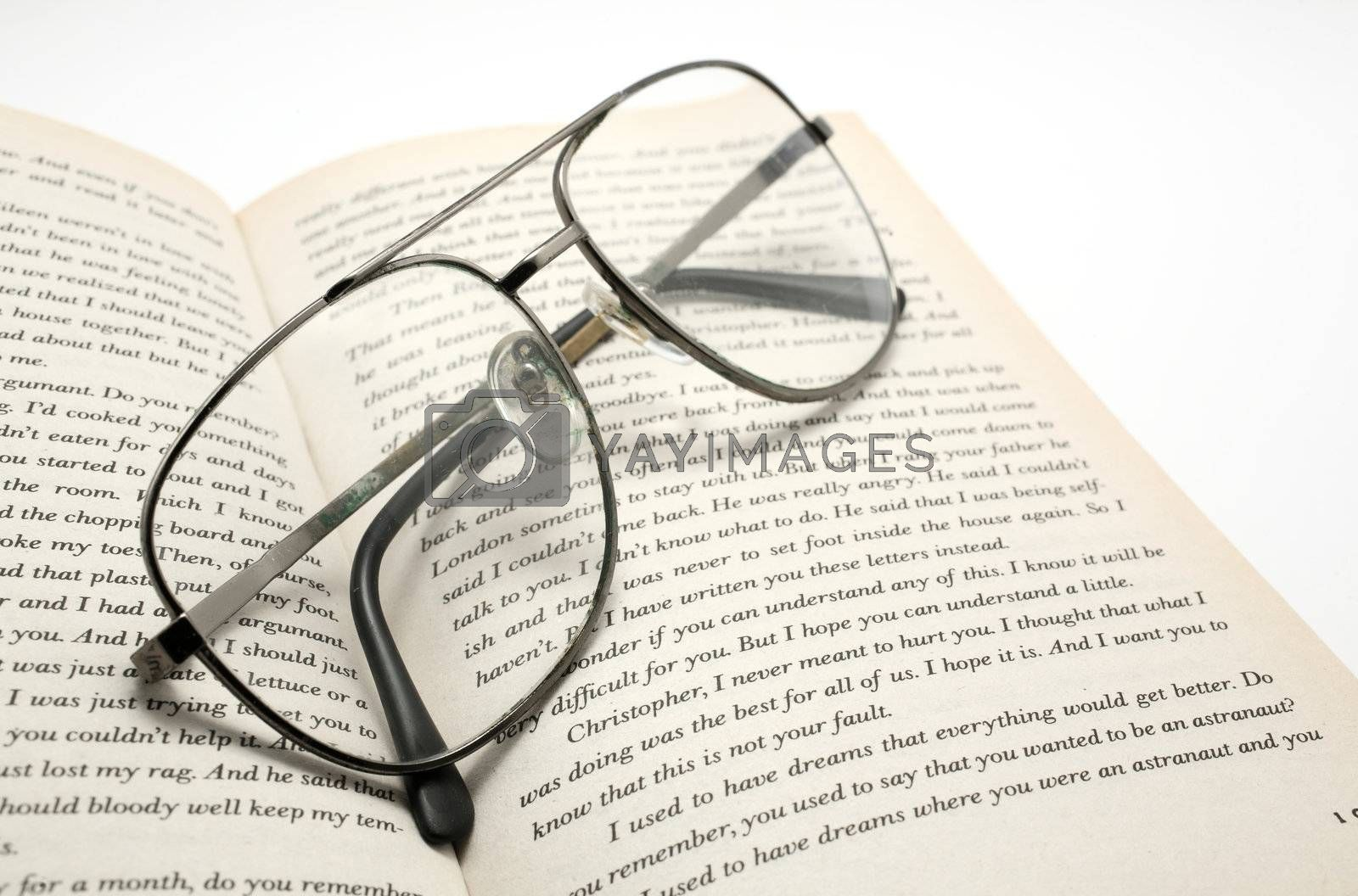 closeup of opened book and glasses  by leungchopan