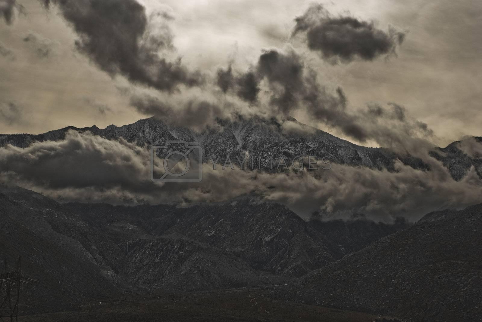 Sun shines through heavy clouds over a mountain