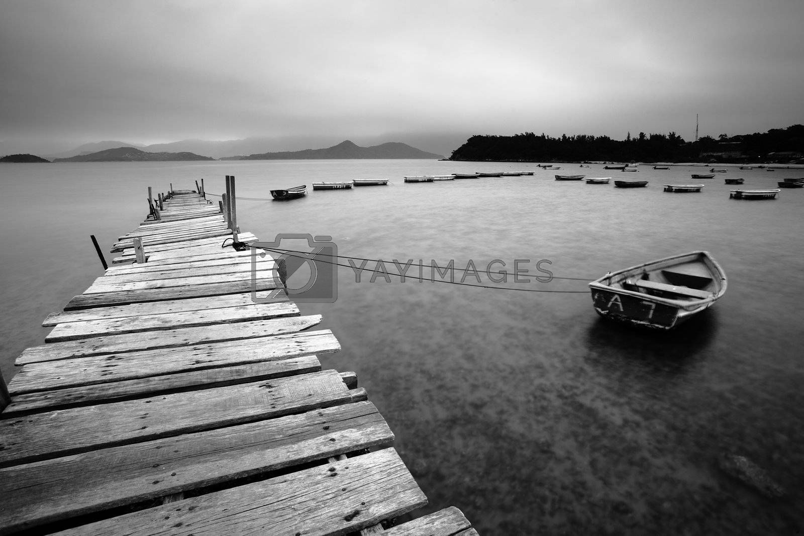Royalty free image of wooden pier and boats by leungchopan
