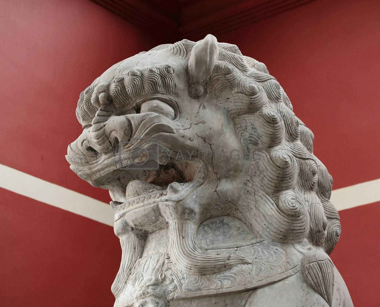 Royalty free image of stone lion statue before the red wall by leungchopan