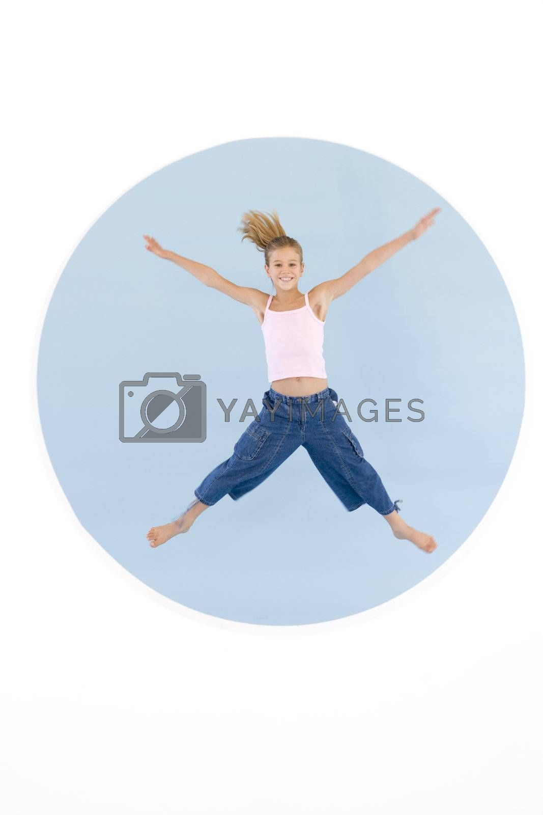 Young girl jumping with arms out smiling