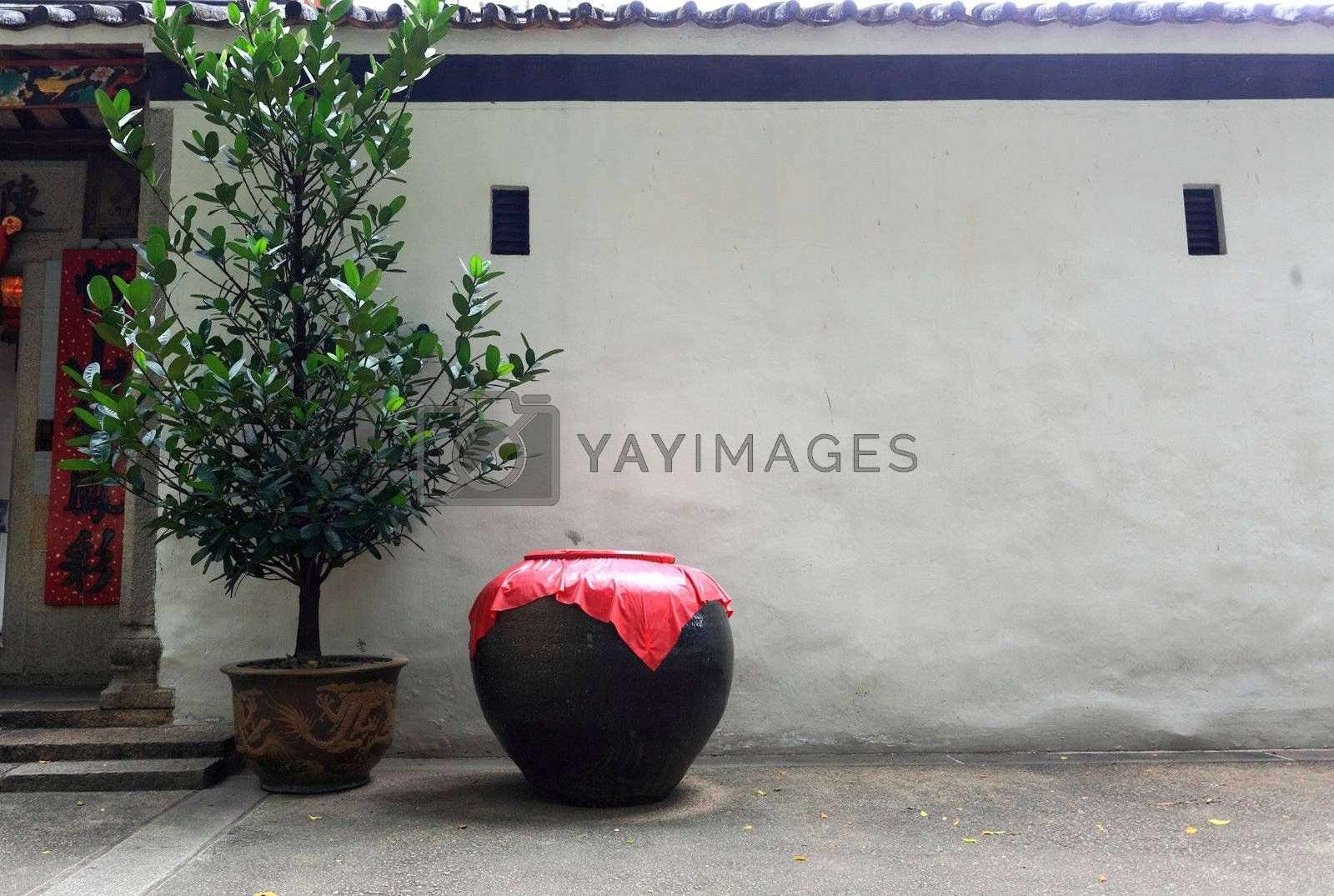 Asian style ceramic pot in frount of the white wall by leungchopan