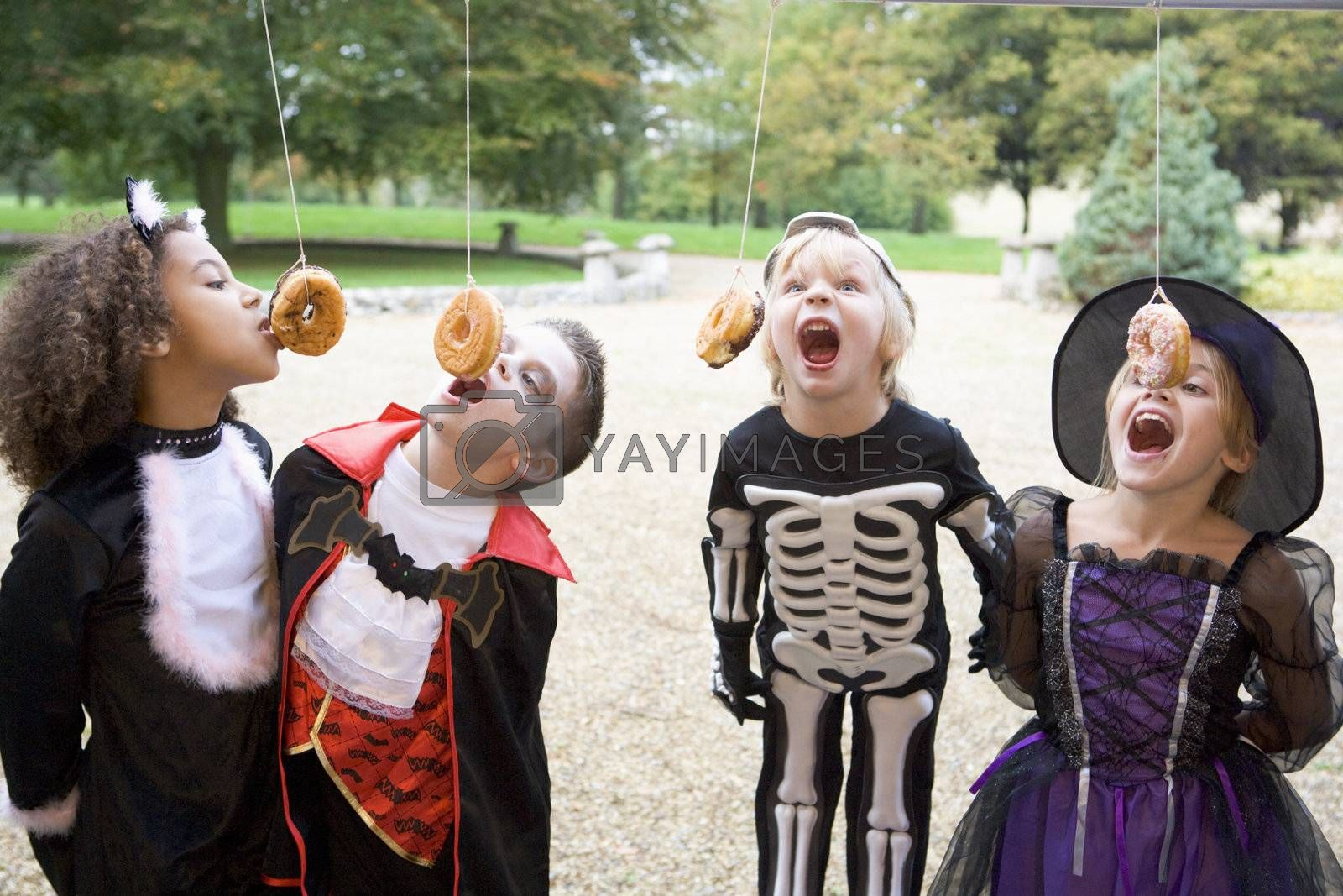 Four young friends on Halloween in costumes eating donuts hangin by MonkeyBusiness