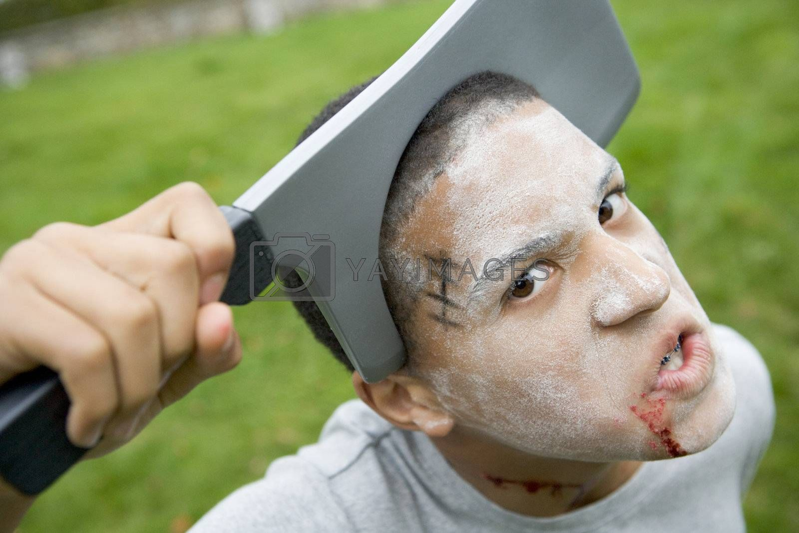 Young boy with scary Halloween make up and plastic knife through by MonkeyBusiness