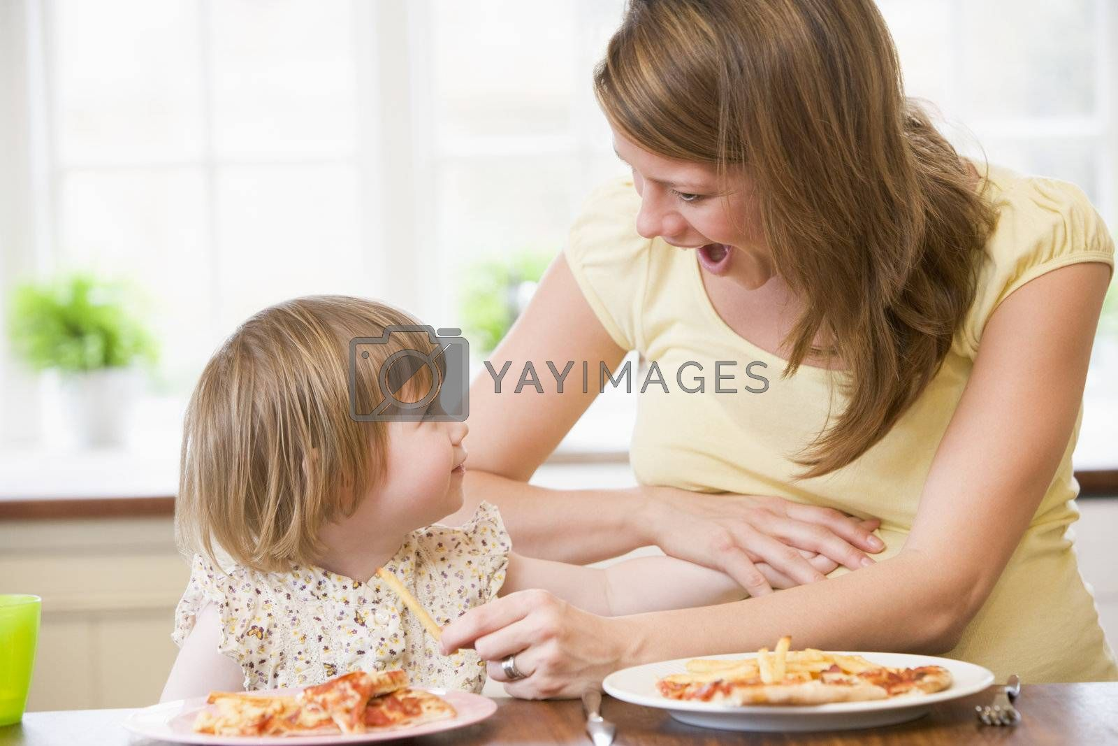 Pregnant mother with daughter touching belly eating French fries by MonkeyBusiness